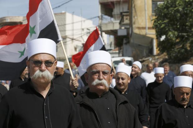 Des habitants druzes du village d'Ein Qiniye, situé sur le plateau du Golan sous occupation israélienne, brandissent des drapeaux syriens alors qu'ils manifestent lors d'un rassemblement marquant le Jour de l'indépendance de la Syrie (AFP)