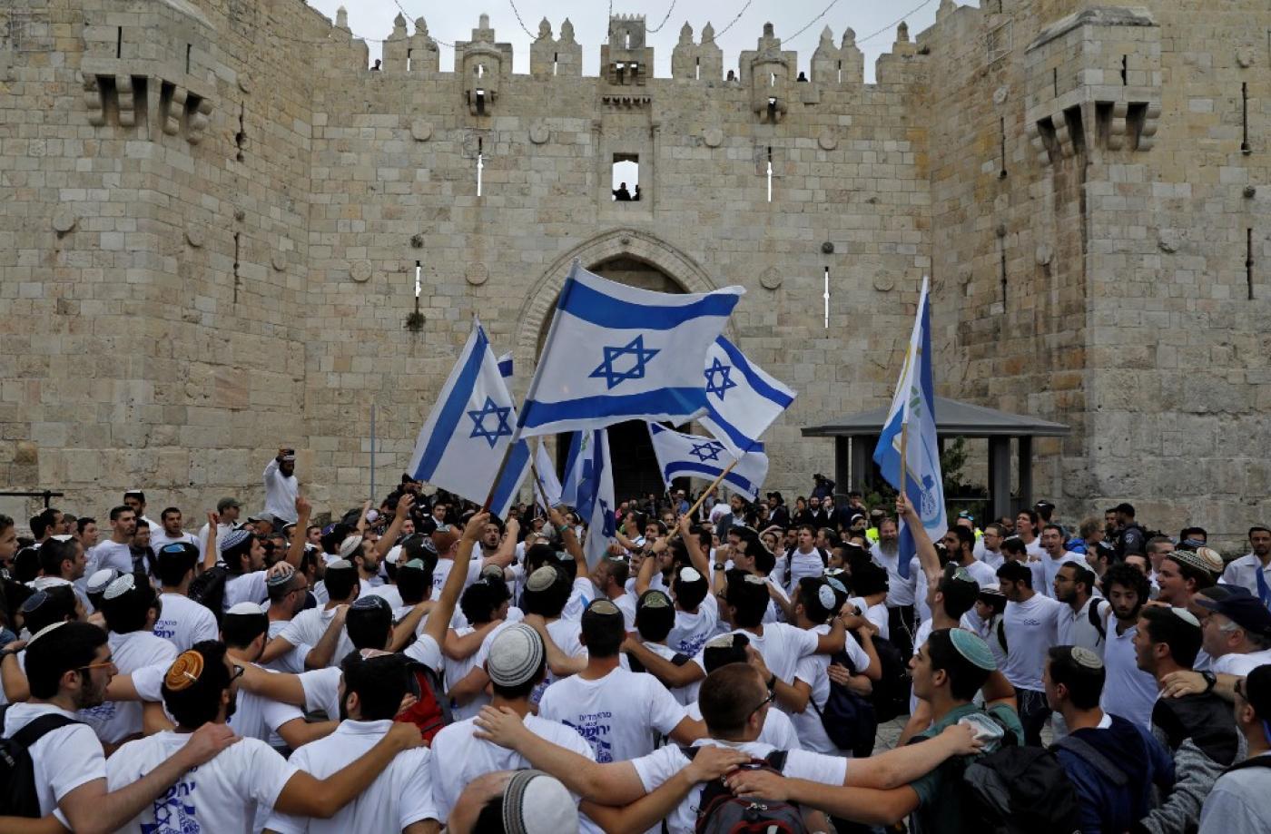 Des colons agitent des drapeaux israéliens alors qu'ils célèbrent la Journée de Jérusalem au niveau de la porte de Damas de la vieille ville, en mai2018 (AFP)