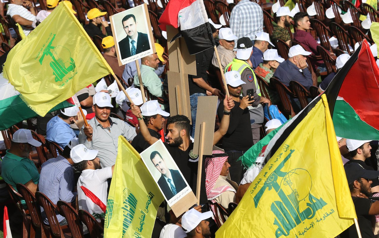 Lebanese Shia Muslims carry pictures of Syrian president Bashar al-Assad, flags of the Hezbollah movement (yellow) during a Quds Day march in Lebanon (AFP)
