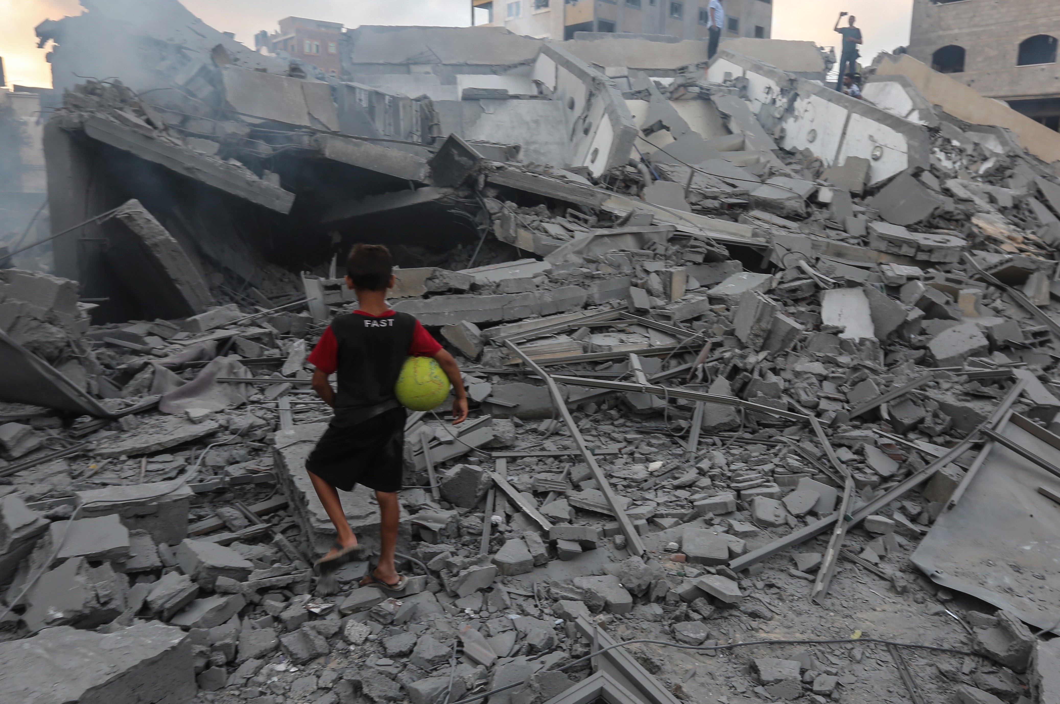 A boy looking at the rubble of the Said al-Mishal Cultural Centre following an Israeli air strike on Gaza City on 9 August 9, 2018 (AFP)
