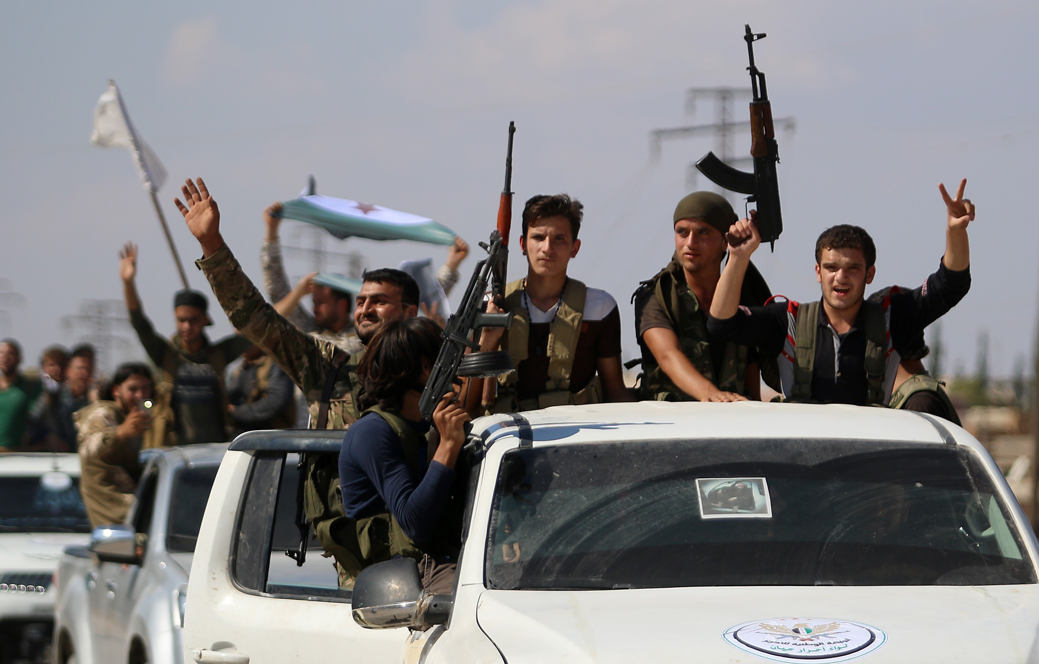 "Syrian rebel fighters from the recently-formed ""National Liberation Front"" parade following military training in Idlib province on 11 September, 2018 (AFP)"
