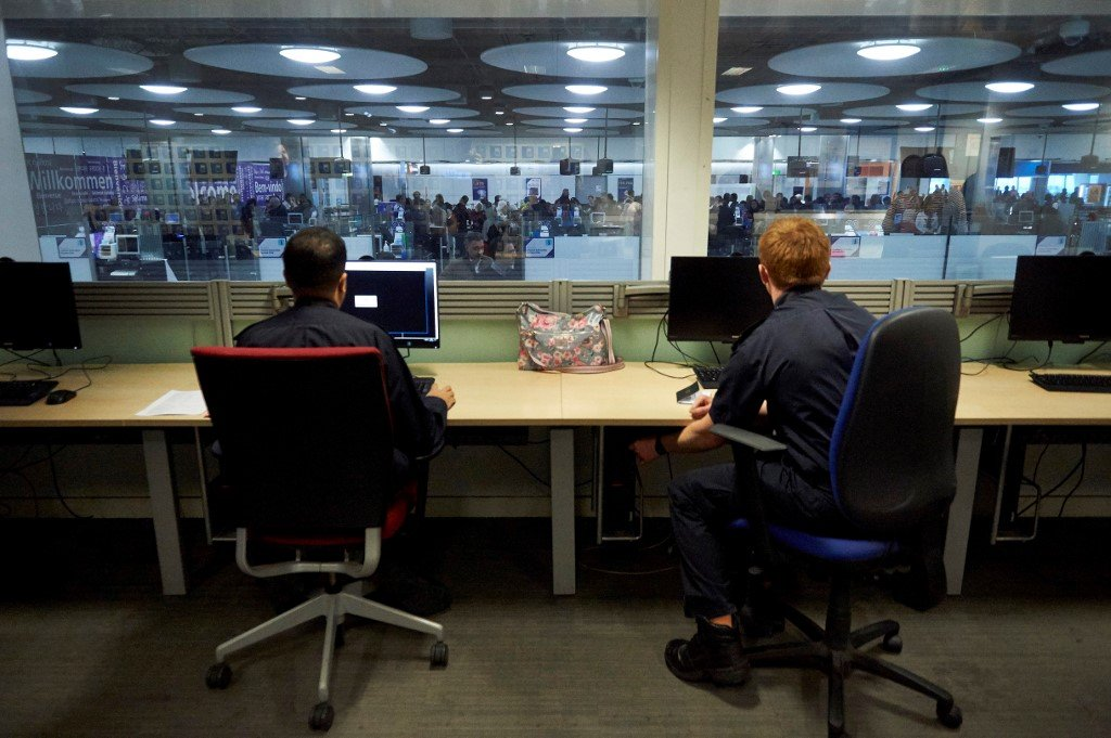 UK Border Force officers work in the watch room overlooking immigration control at Terminal 5 of London Heathrow Airport in west London on 19 December 2018 (AFP)