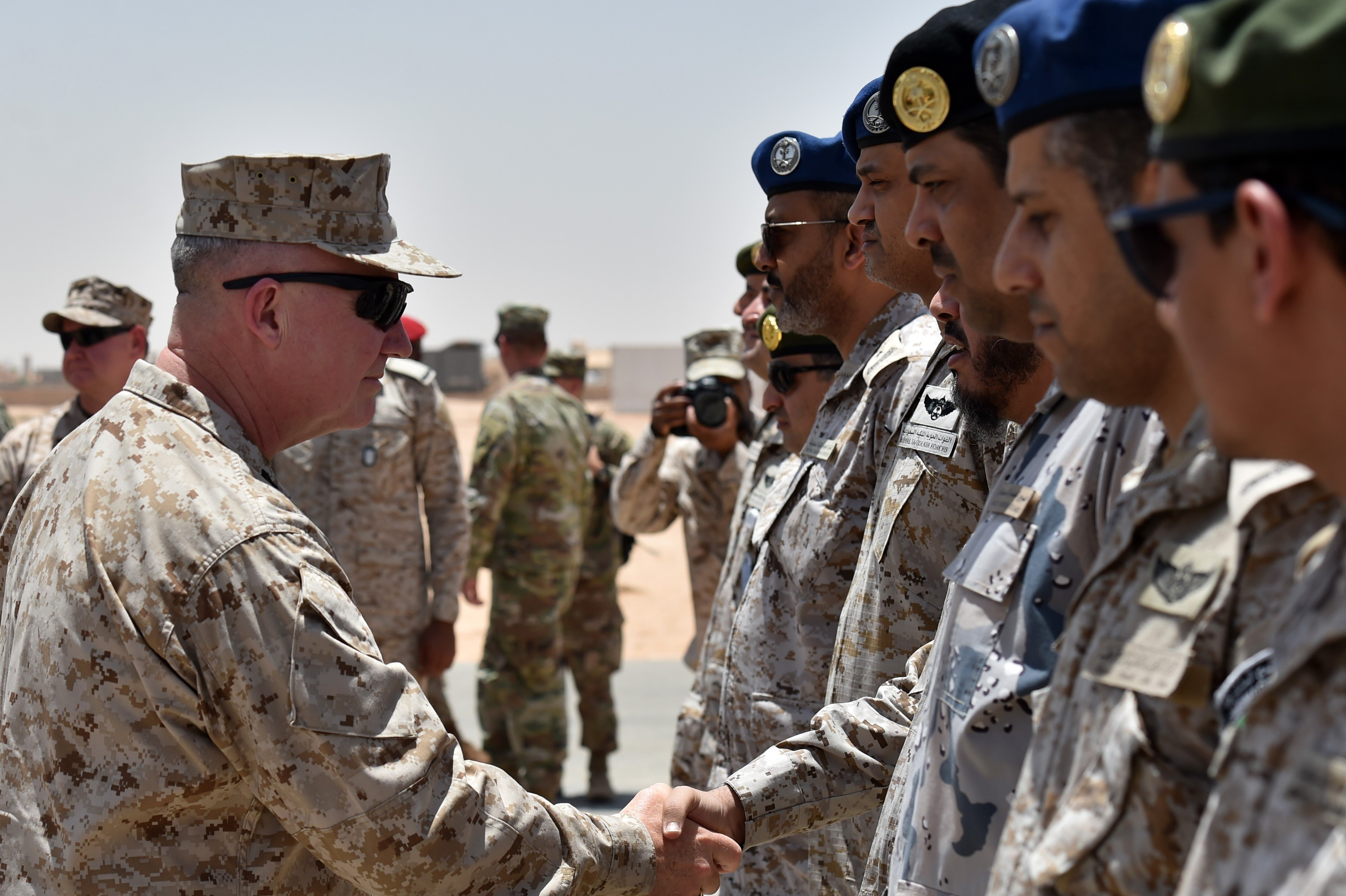 US Marine Corps General Kenneth F. McKenzie Jr. (L), Commander of the US Central Command (CENTCOM), shakes hands with Saudi military officers during his visit to a military base in al-Kharj in central Saudi Arabia on July 18, 2019.