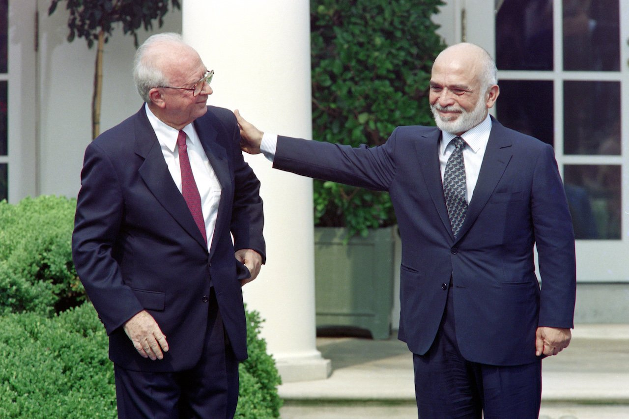 King Hussein of Jordan (R) pats on the shoulder Israeli Prime Minister Yitzhak Rabin at the White House Rose Garden in Washington on 25 July 1994 (AFP)