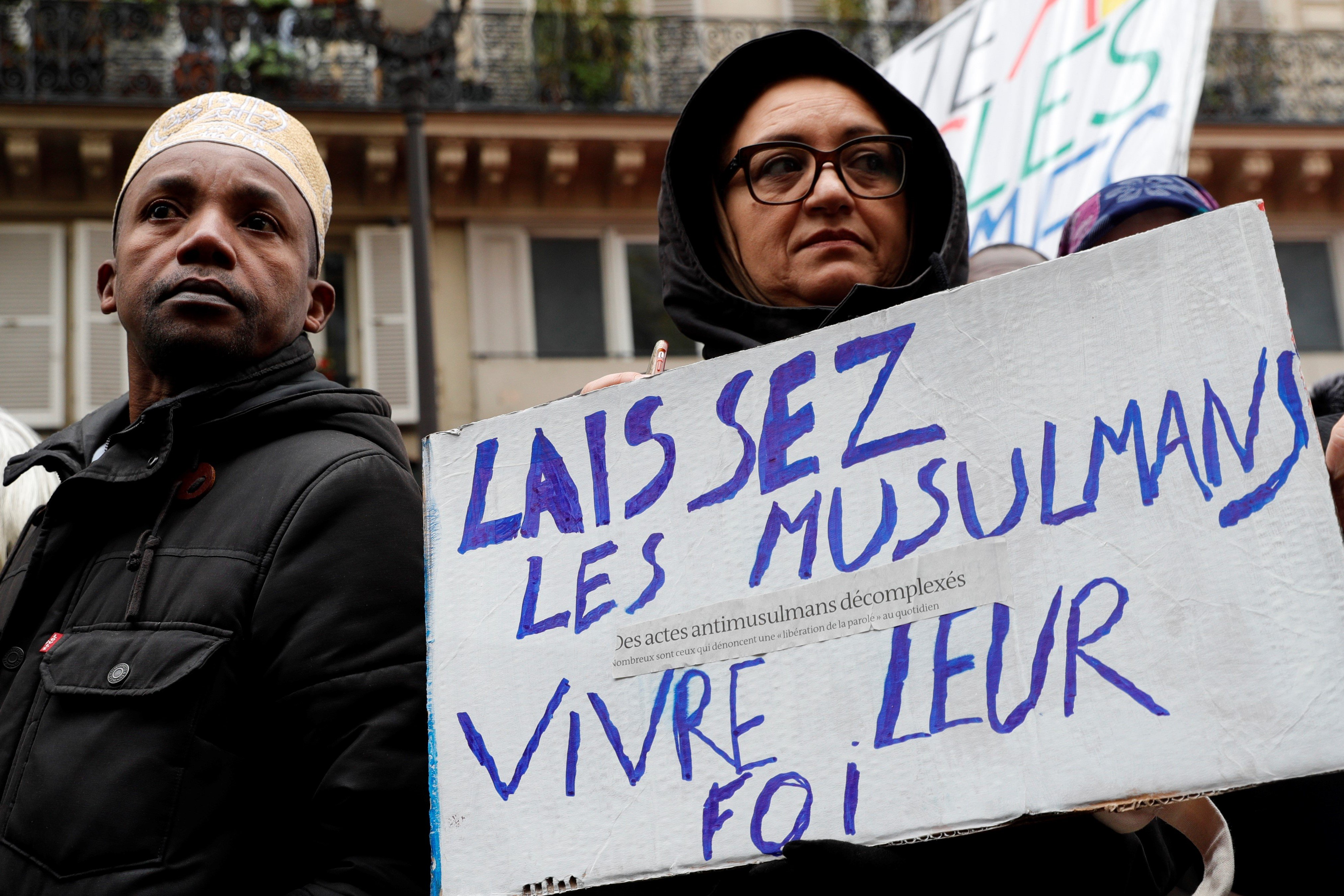 "A woman holds a placard reading ""Let Muslims live their faith"" as she takes part in a demonstration march in front of the Gare du Nord, in Paris to protest against Islamophobia, on November 10, 2019."