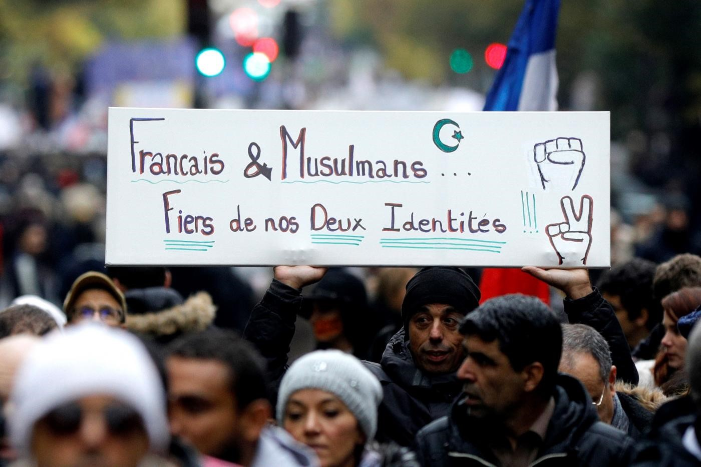 "Protesters hold a placard reading ""French and Muslims, proud of our identities"" as they march in Paris to protest against Islamophobia, on 10 November 2019 (AFP"