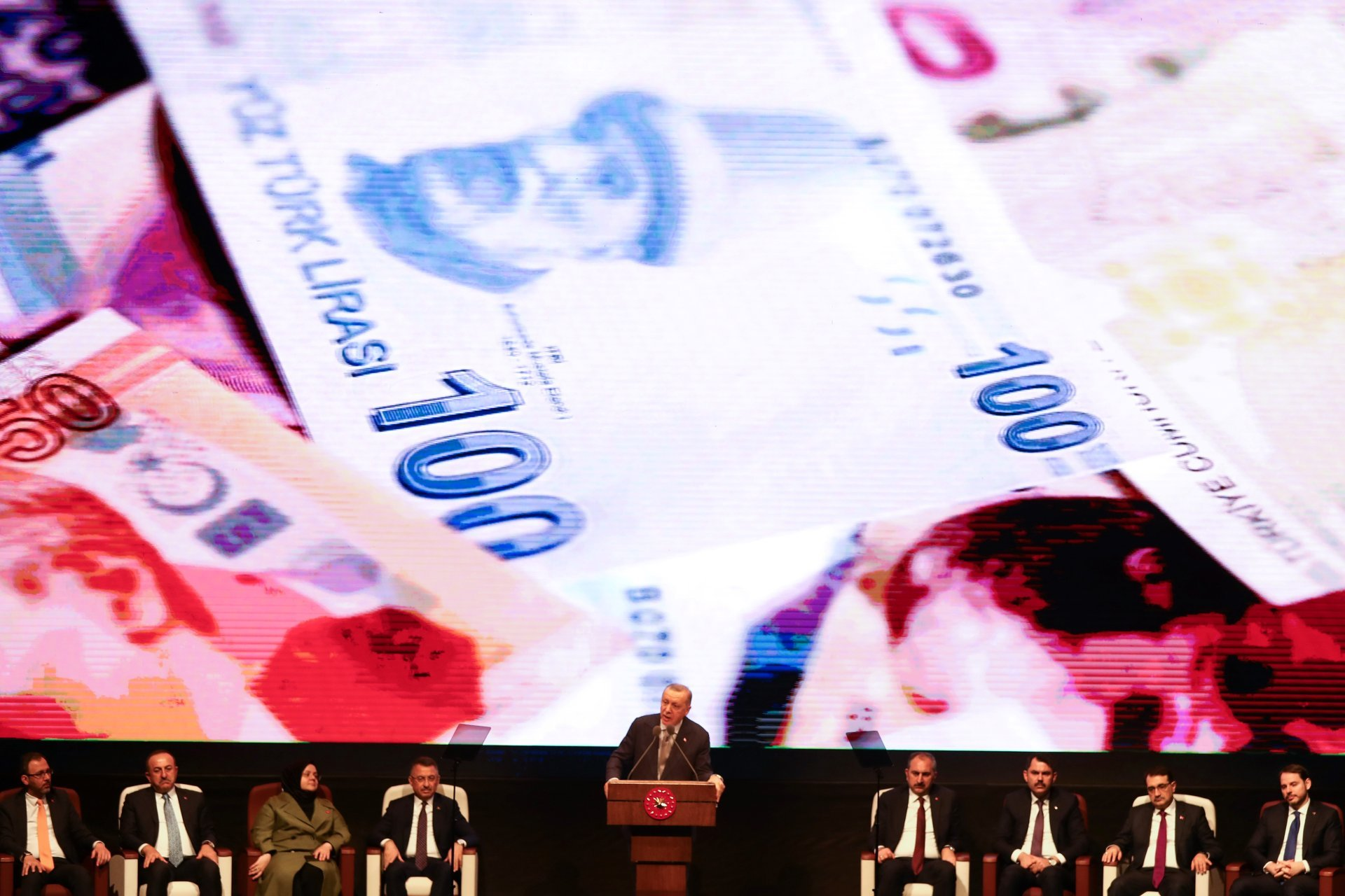 Turkish President Recep Tayyip Erdogan gestures as he delivers a speech on stage, with on the background banknotes of the Turkish lira (AFP)