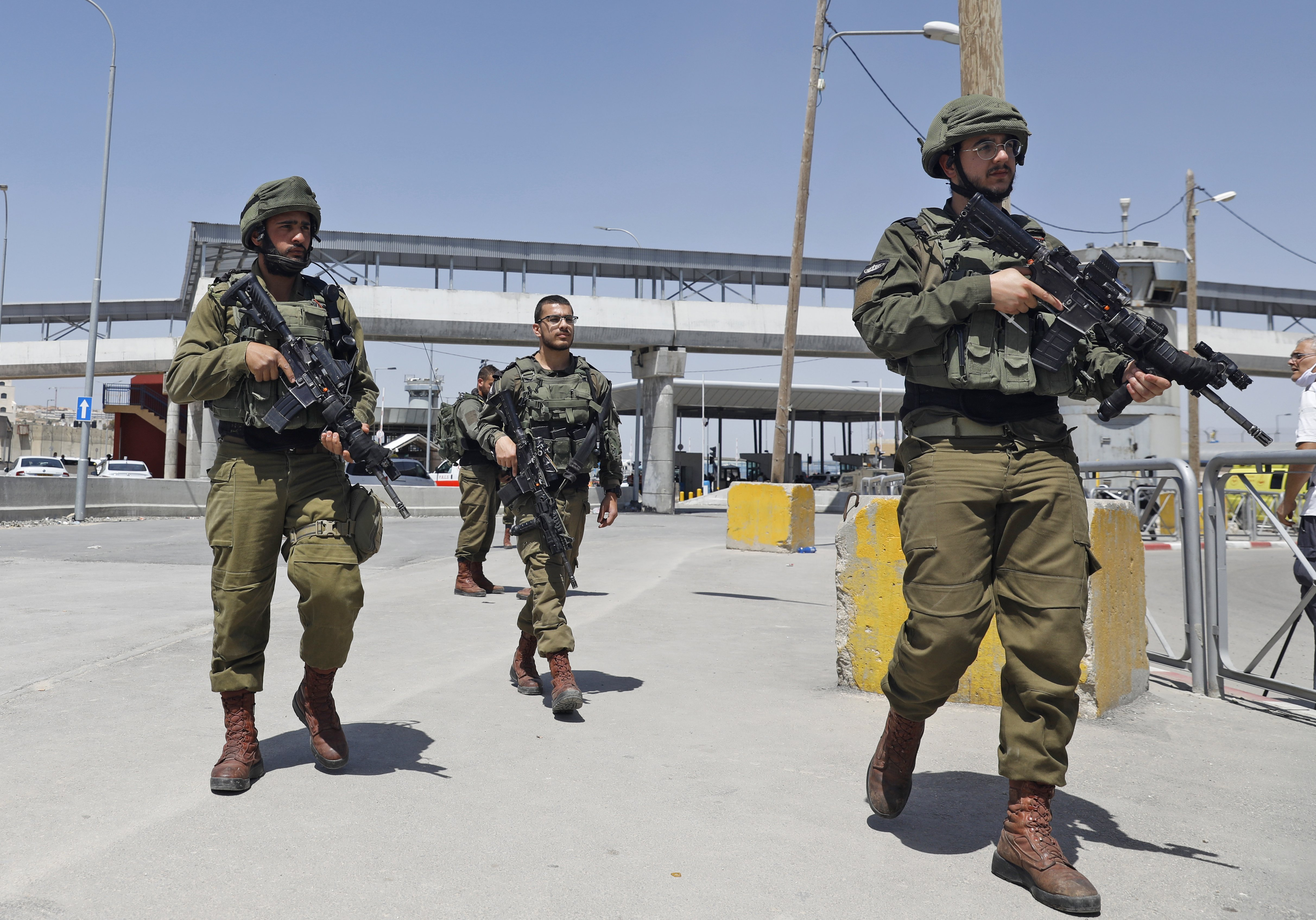 Israeli soldiers gather at a checkpoint in the occupied West Bank in May 2020 (AFP)