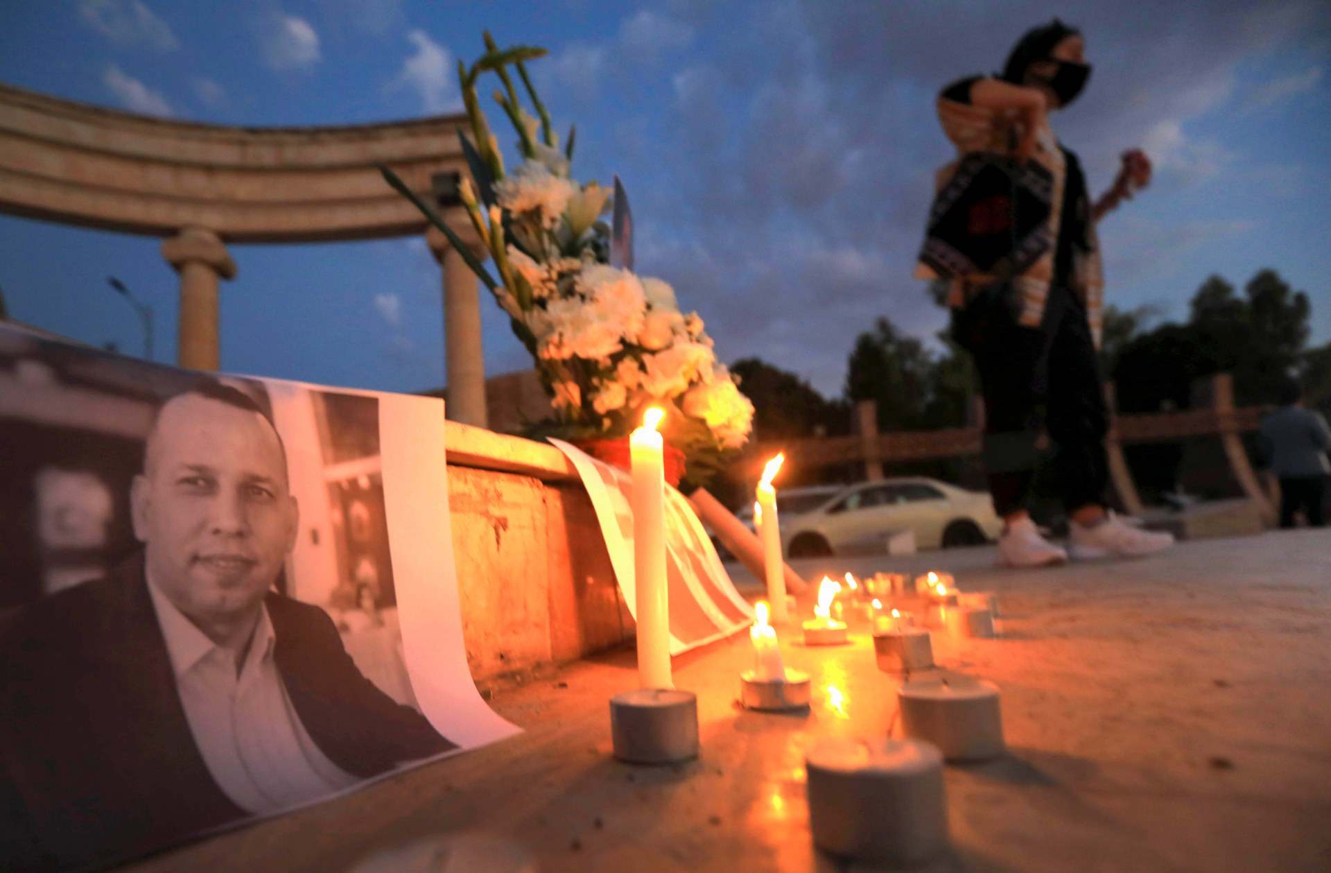 An Iraqi places a candle in front of a poster of slain Iraqi jihadism expert Hisham al-Hashemi during a candlelight vigil in Erbil (AFP)