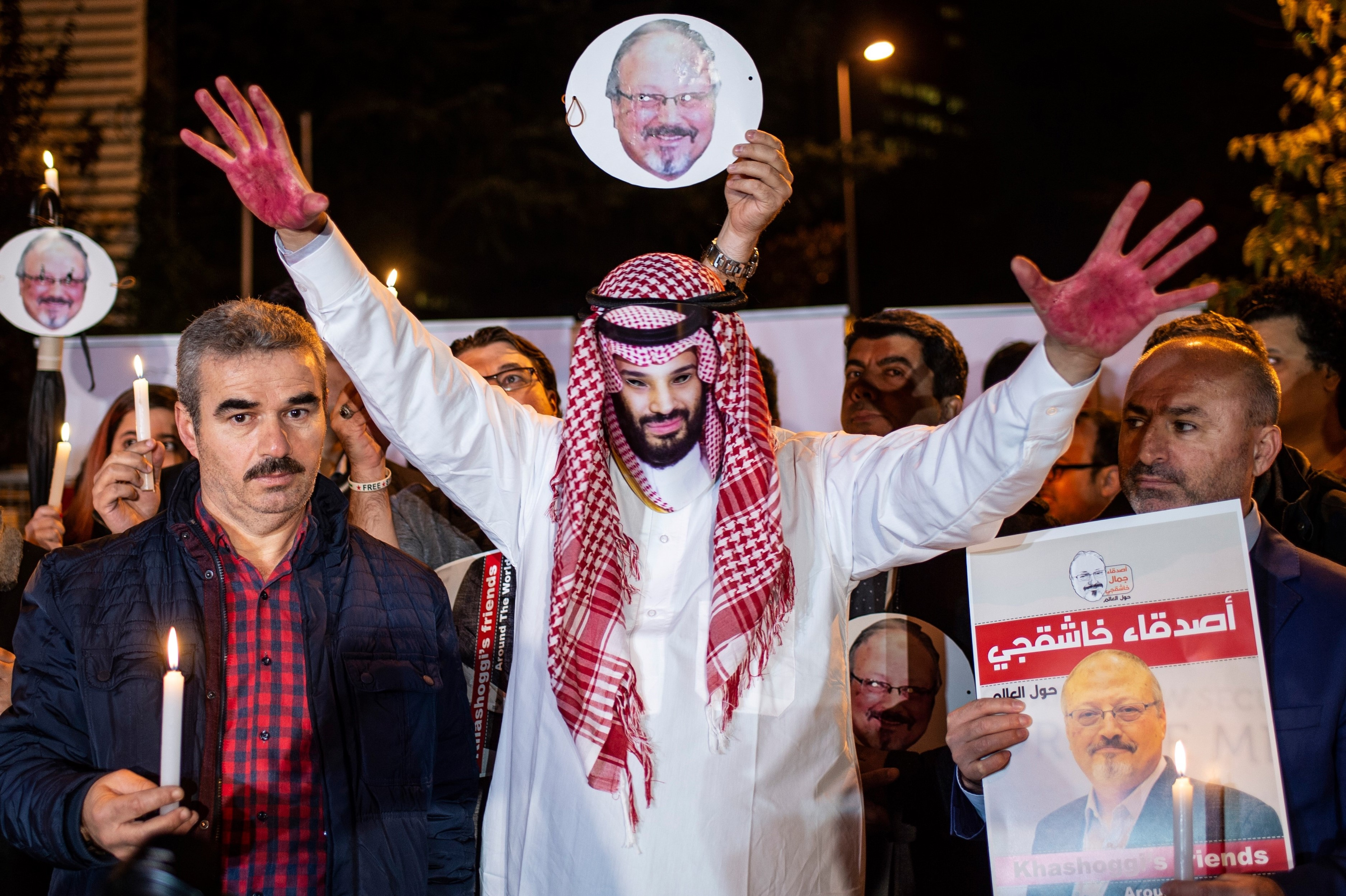 A protestor wears a mask of depicting Saudi Crown Prince Mohammad Bin Salman with red painted hands next to people holding posters of Saudi journalist Jamal Khashoggi during the demonstration outside the Saudi Arabia consulate in Istanbul, on 25 October, 2018 (AFP)