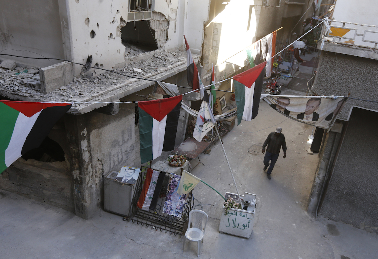 A man walks past destroyed buildings decorated with Palestinian flags in the Palestinian camp of Yarmuk southern Damascus (AFP)