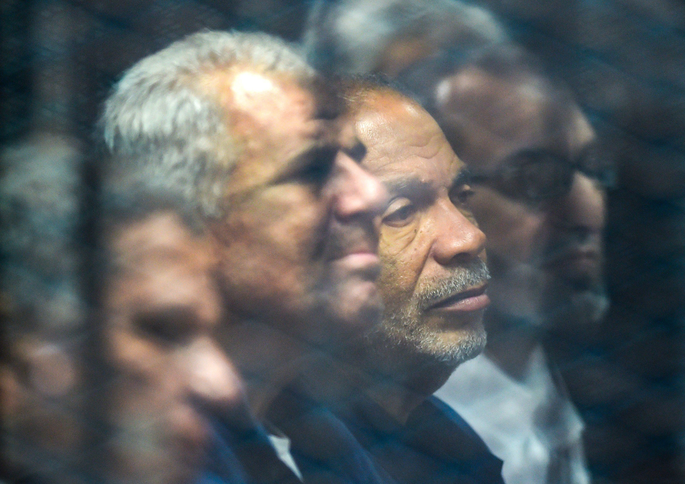 Senior Muslim Brotherhood members behind bars at a make-shift courthouse in southern Cairo on 2 December, 2018 (AFP)