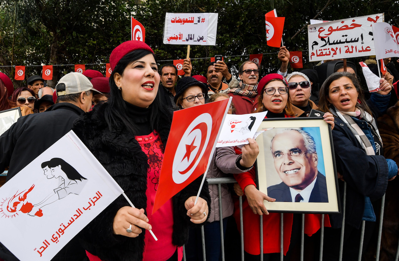 Abir Moussi, president of Tunisia's Free Destourian Party (Free Constitutional Party) shouts slogans as another colleague holds up a portrait of late president Habib Bourguiba during a protest against the Truth and Dignity Commission (TDC) outside its closing conference in the capital Tunis on December 14, 2018. The Truth and Dignity Institute