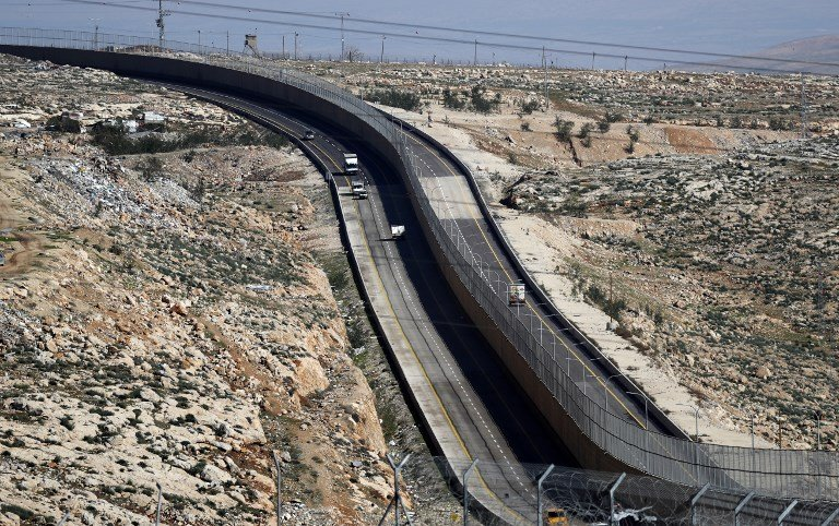 'Apartheid Road' has a wall along its length, dividing Palestinian and Israeli drivers (AFP)
