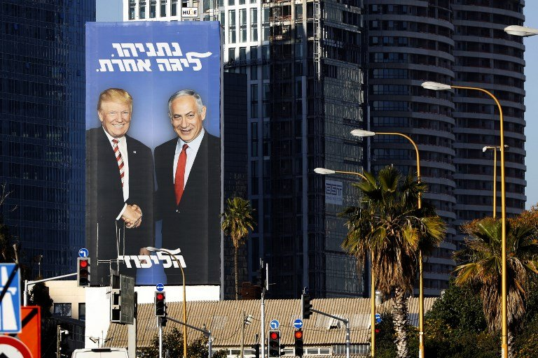 An election billboard shows Israeli Prime Minister Benjamin Netanyahu shaking hands with US President Donald Trump in Tel Aviv on 3 February (AFP)