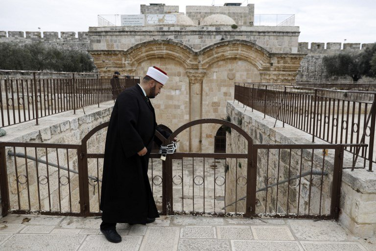 A Muslim man checks a gate closed by Israeli police at al-Aqsa Mosque compound in Jerusalem's Old City on 18 February (AFP)