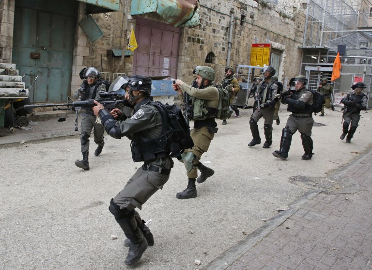 Israeli soldiers shoot rubber-coated metal bullets at Palestinian protesters in Hebron on 22 February (AFP)