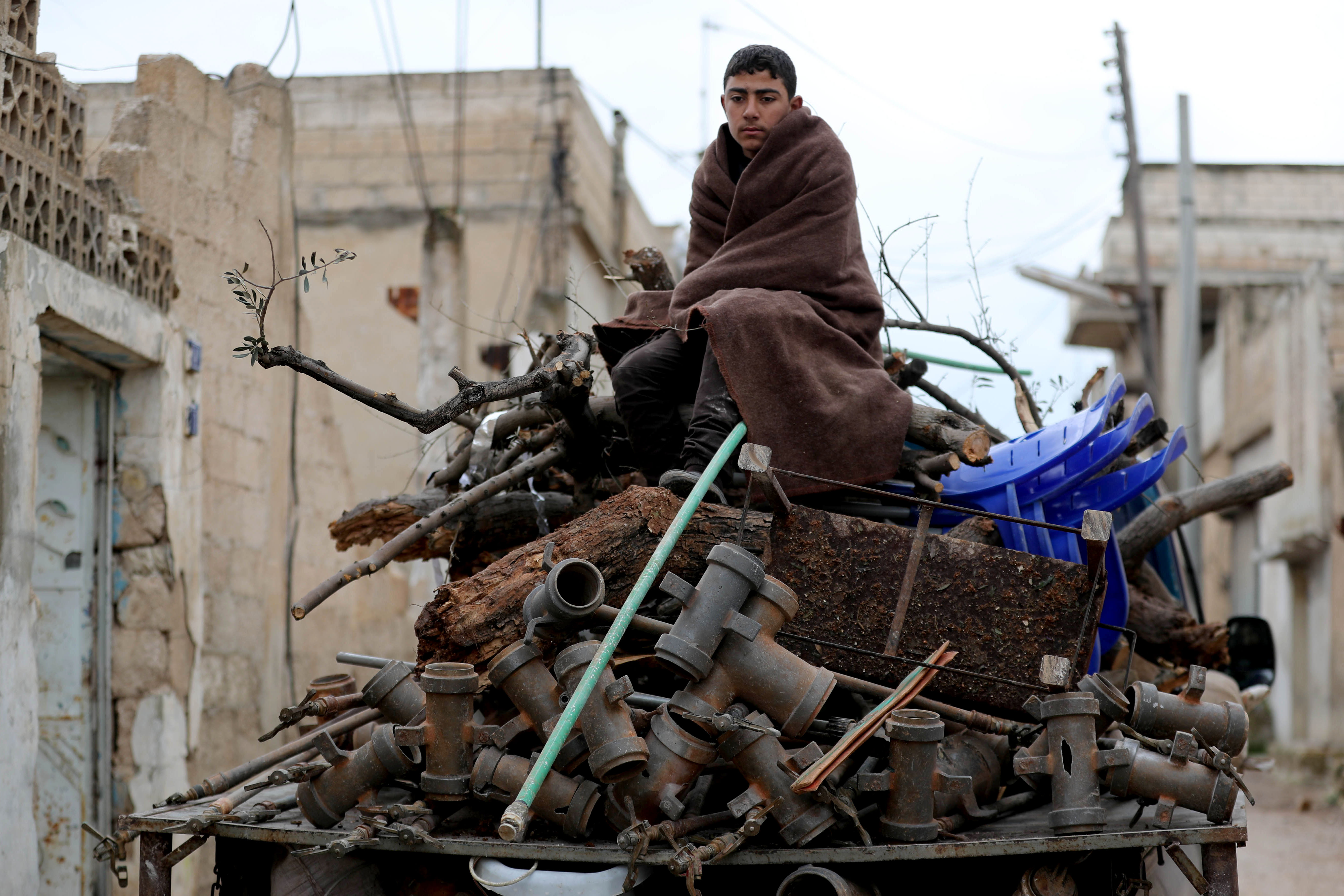 A Syrian youth prepares to flee Khan Sheikhun on 28 February (AFP)