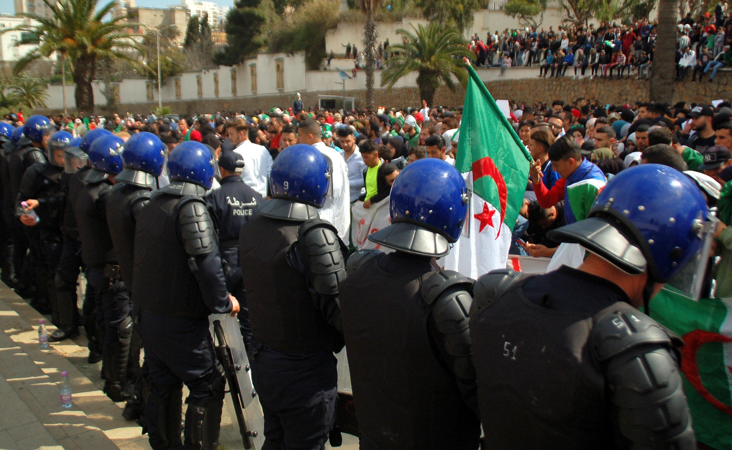 Algerian police stand guard during a protest in Oran on 5 March (AFP)