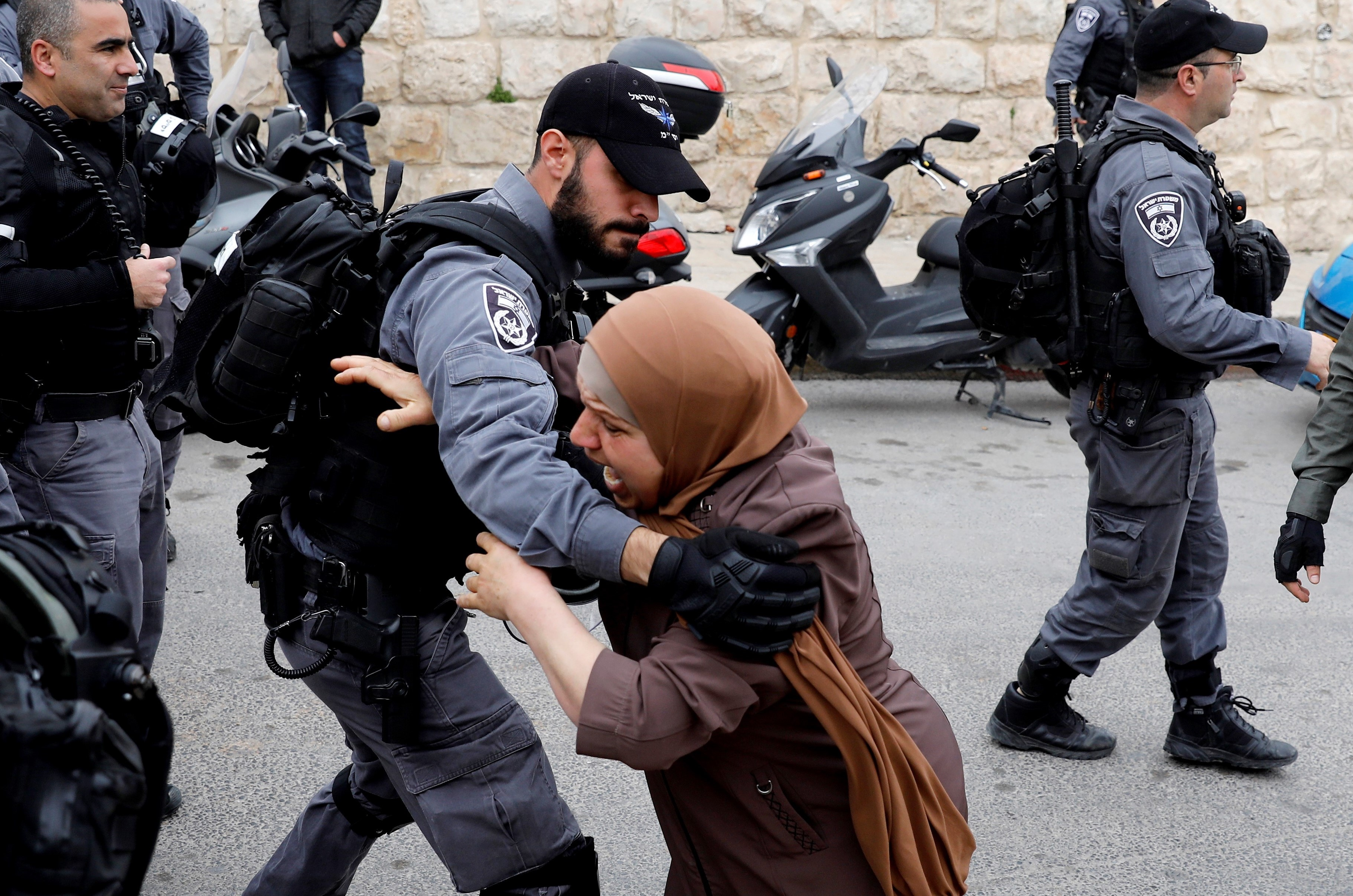 An Israeli policeman pushes back a Palestinian woman outside the Old City of Jerusalem after Israeli forces closed the entrance to al-Aqsa mosque compound on 12 March (AFP)