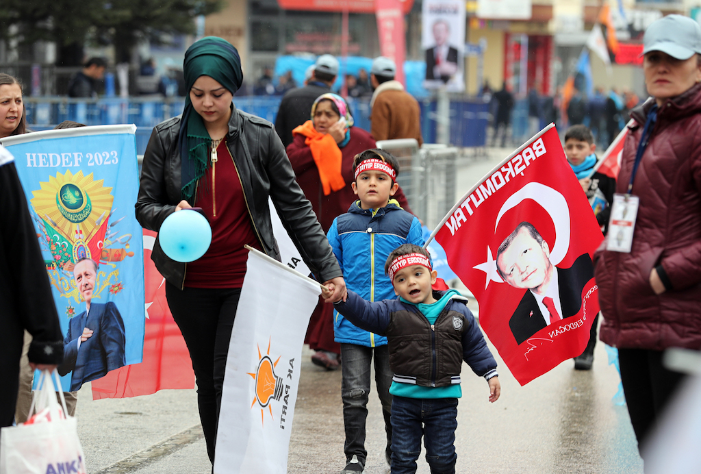 A woman walks with her child as people gather to listen to Turkish President Recep Tayyip Erdogan during a campaign rally of the Turkey's ruling party in Ankara (AFP)