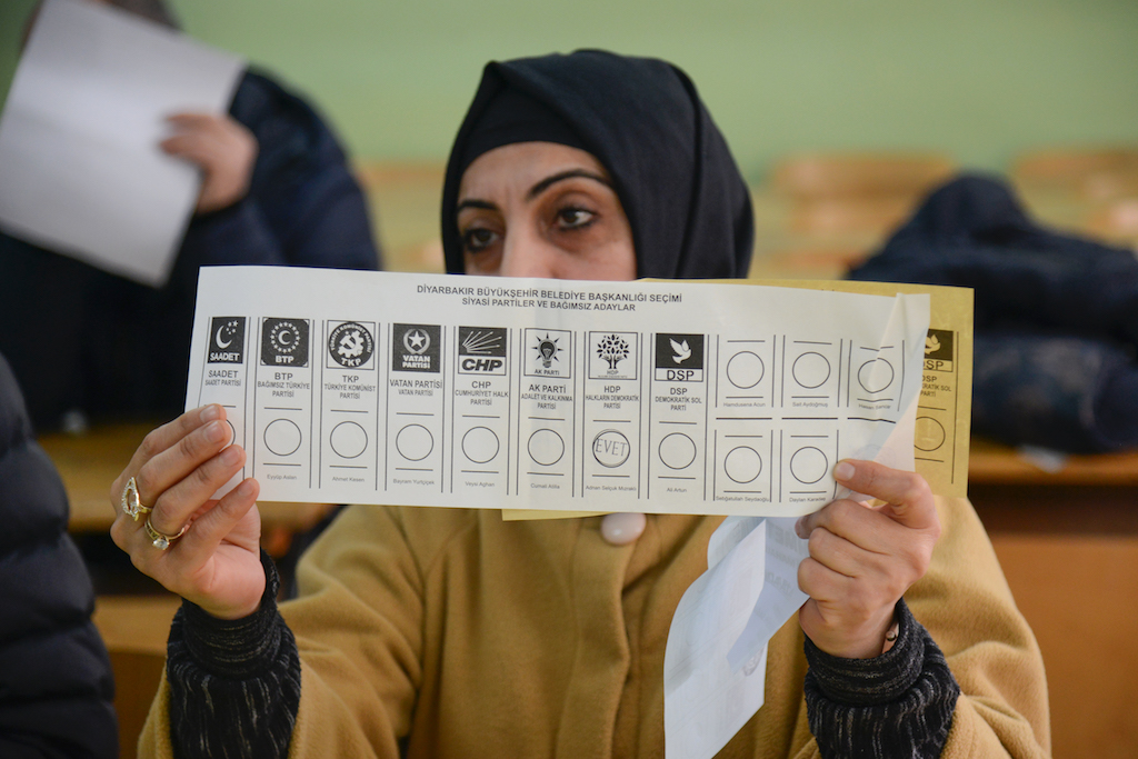 An election official shows a ballot during the counting at a polling station located in a school of Diyarbakir in southeastern Turkey