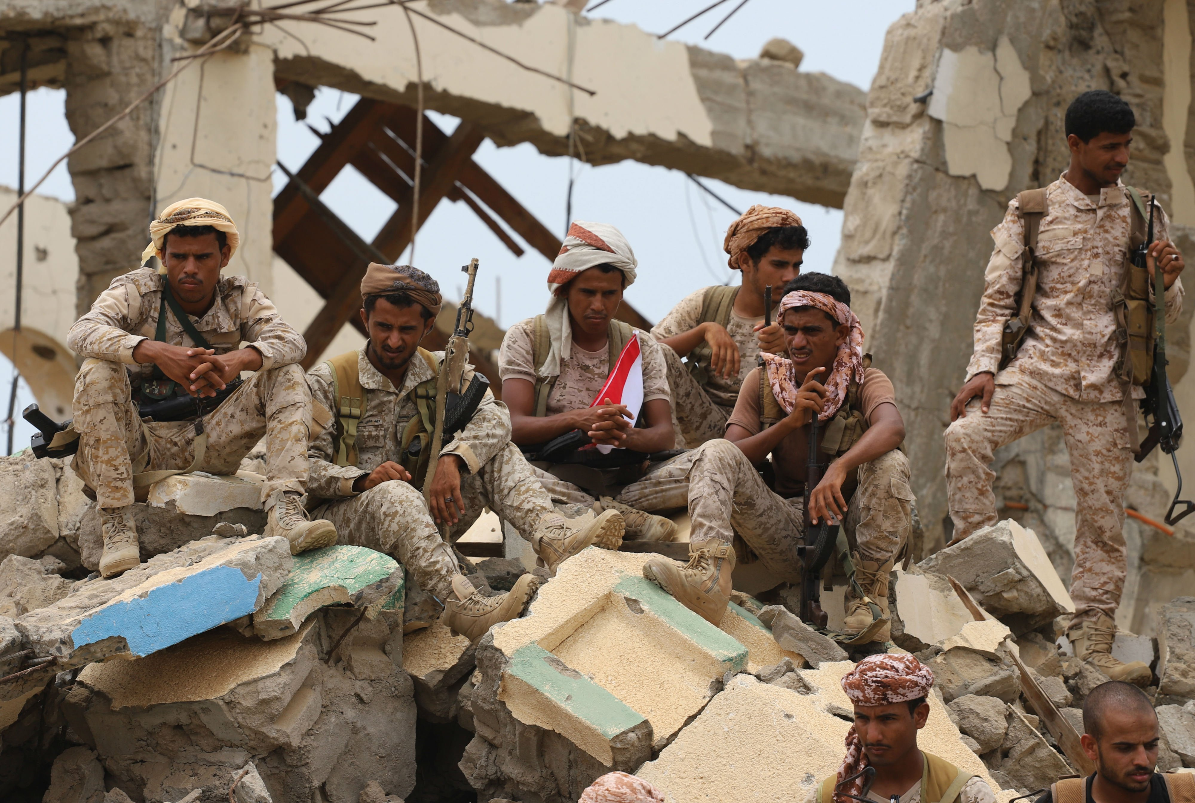Saudi-backed Yemeni fighters gather above debris of a building in Midi (AFP)