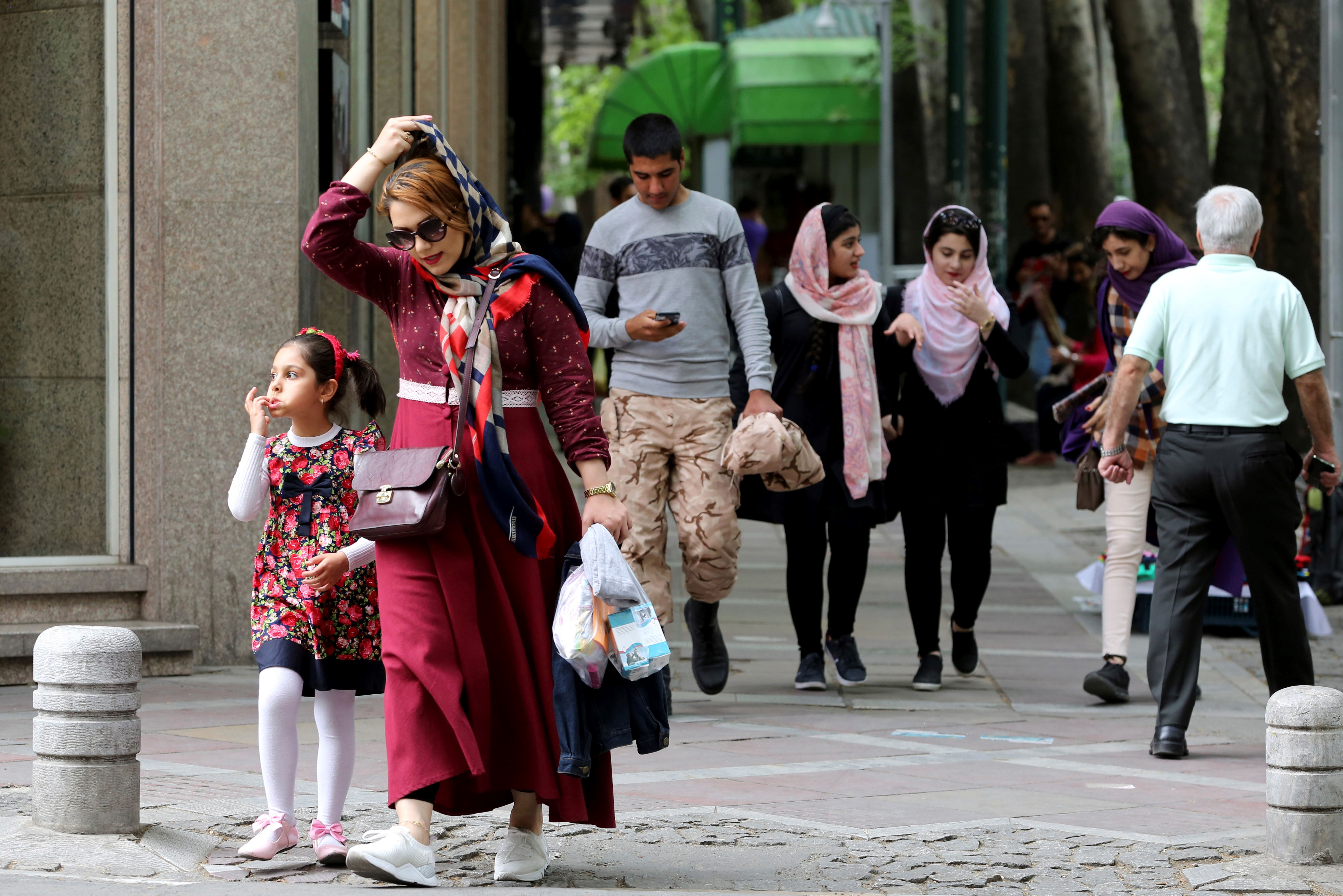 Iranians walk in Valiasr Street in northern Tehran on 8 May (AFP)