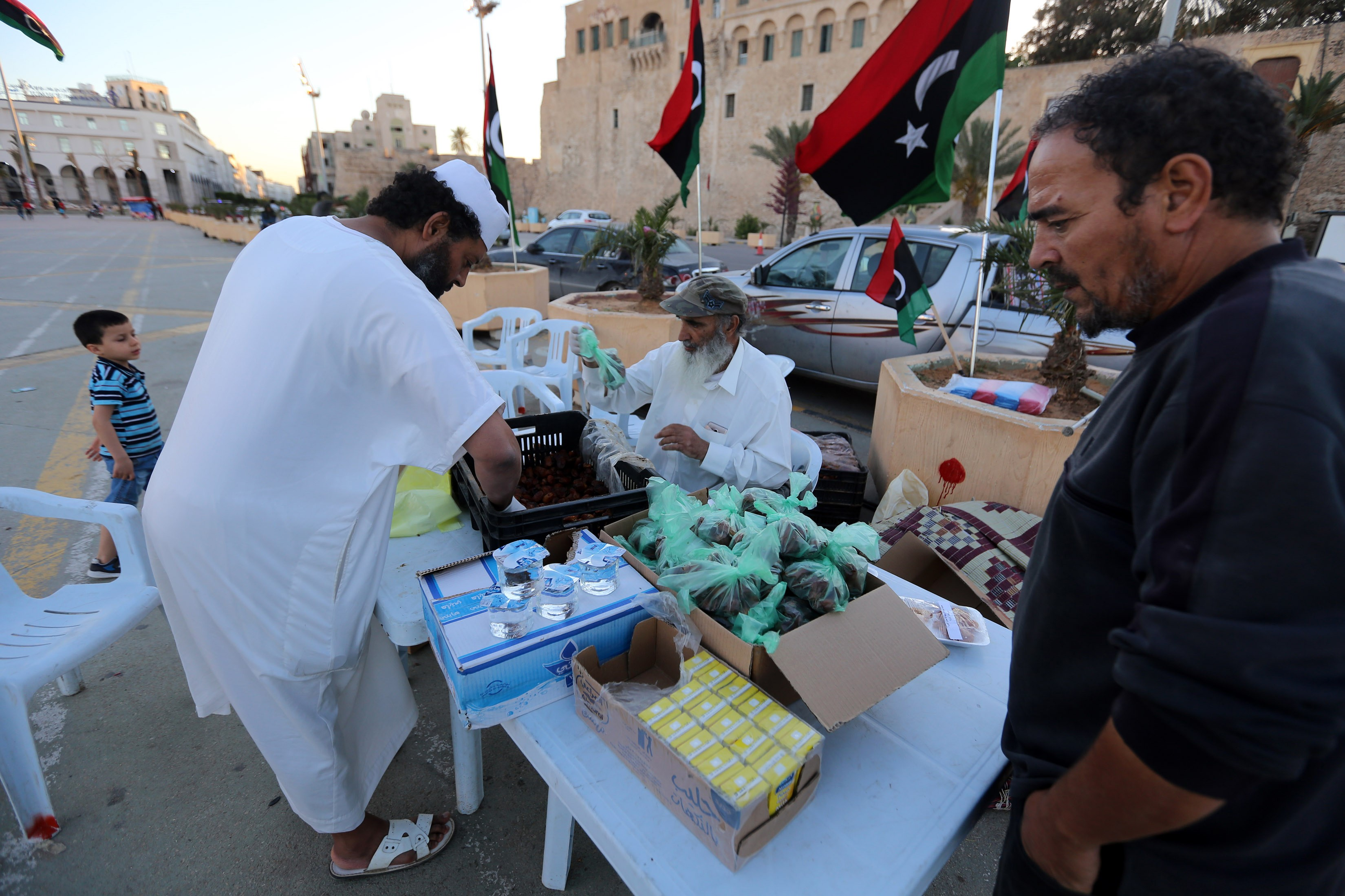 Libyans prepare to distribute snacks and water to people to break their fast during Ramadan in the Martyrs Square of the capital Tripoli, on 15 May (AFP)