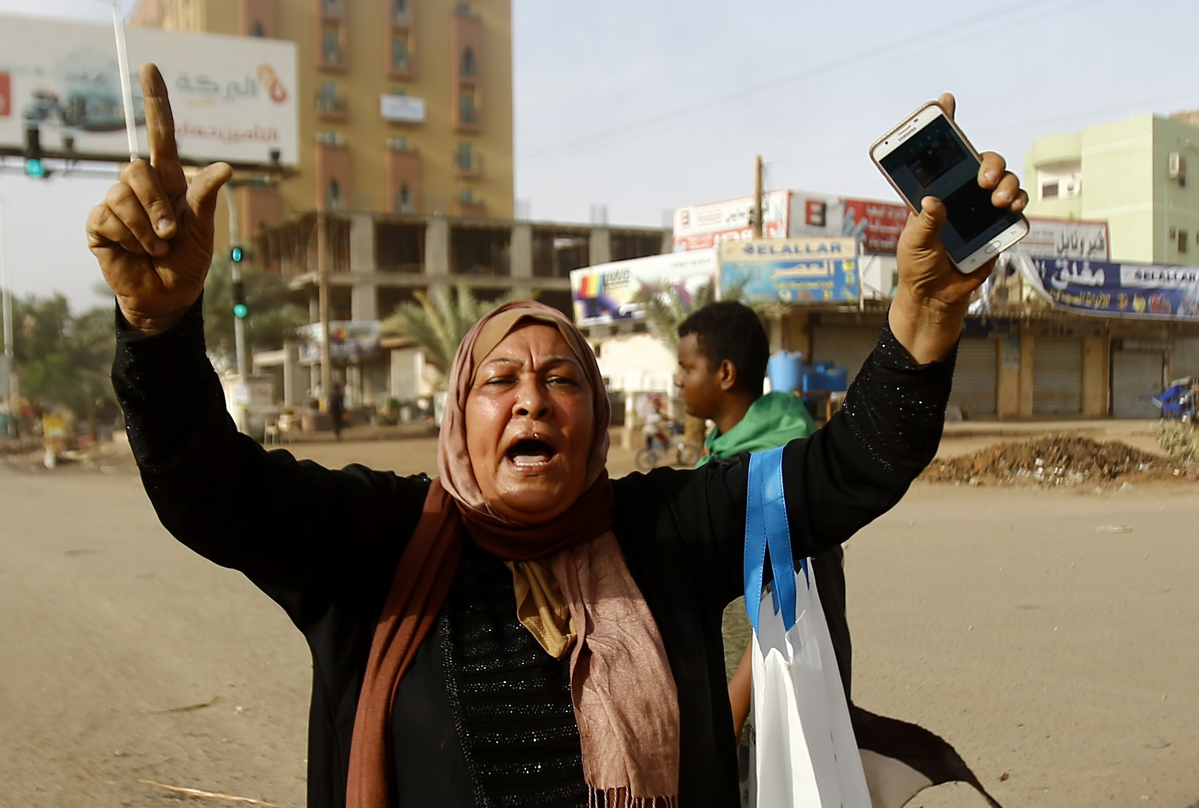 A Sudanese protester reacts as military forces tried to disperse a sit-in outside Khartoum's army headquarters on 3 June (AFP)
