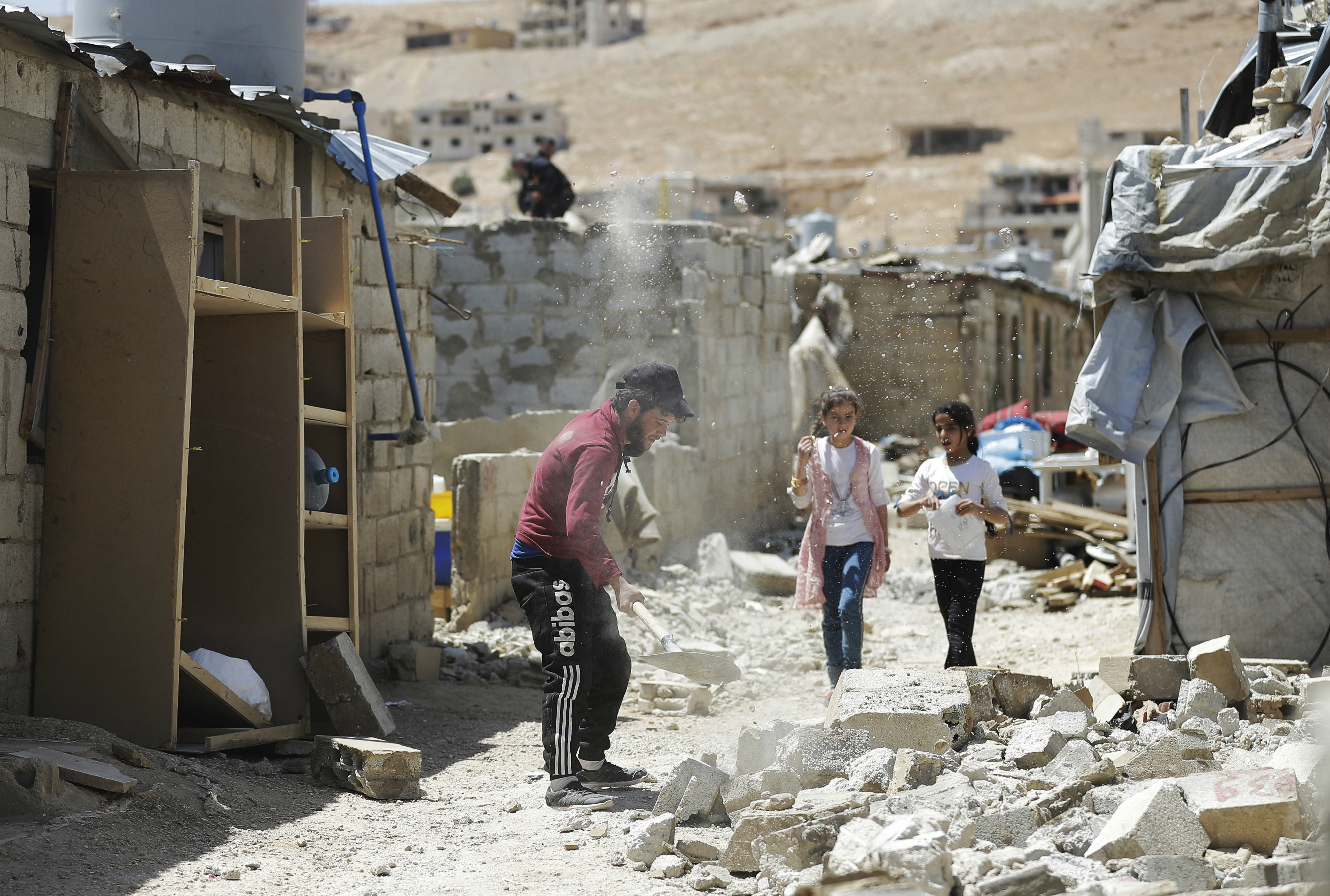 Two girls walking past a demolished schack in a refugee housing in the northeastern Lebanese town of Arsal, in the Bekaa valley (AFP)