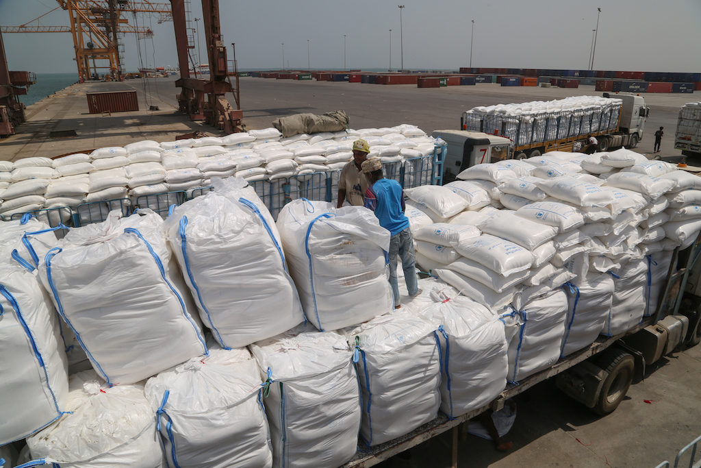 Yemenis receive sacks of food aid packages from the World Food Programme (WFP) in the Yemeni port city of Hodeidah (AFP)