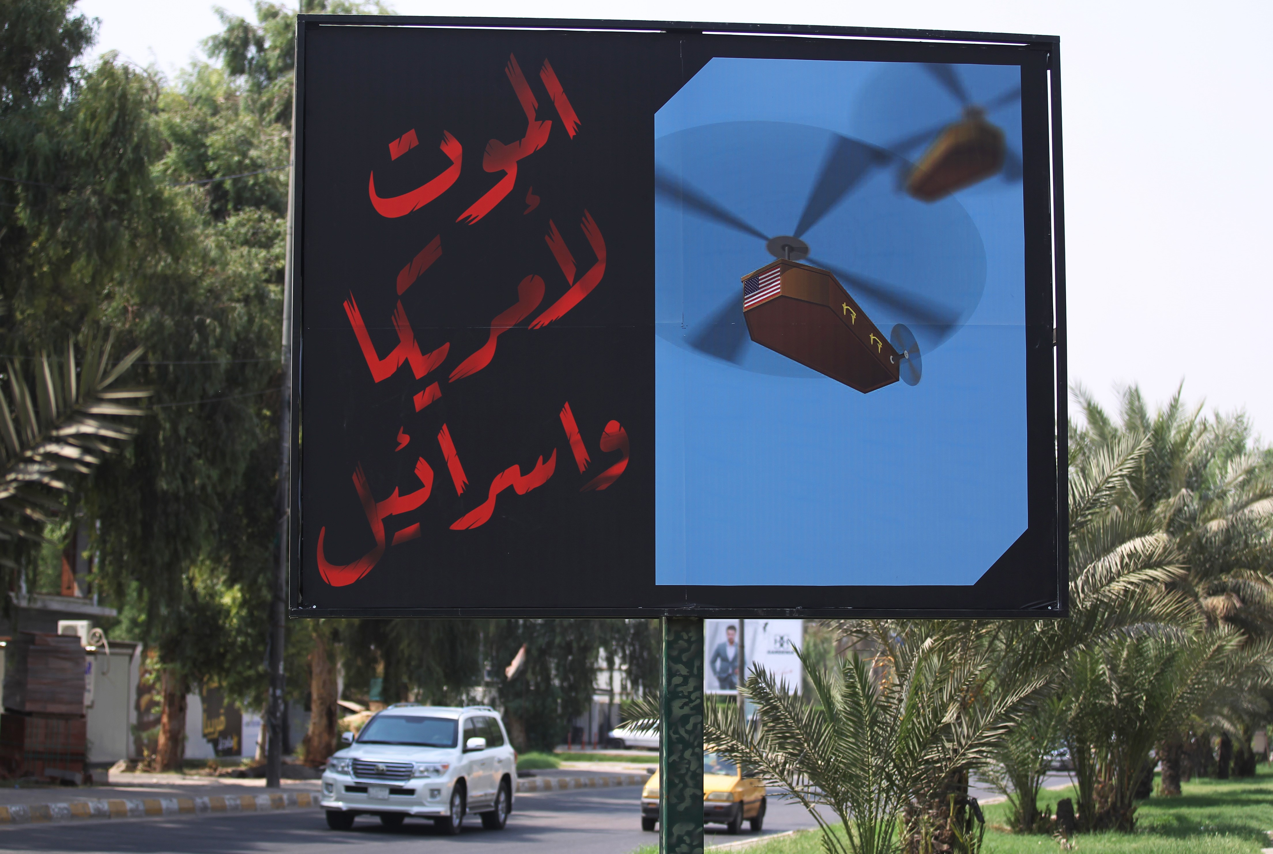 "A billboard installed by members of Iraq's Hashed al-Shaabi on a main road in Baghdad with the slogan: ""Death to America and Israel"" next to a picture of a helicopter carrying a coffin draped with the US flag on 30 August (AFP)"