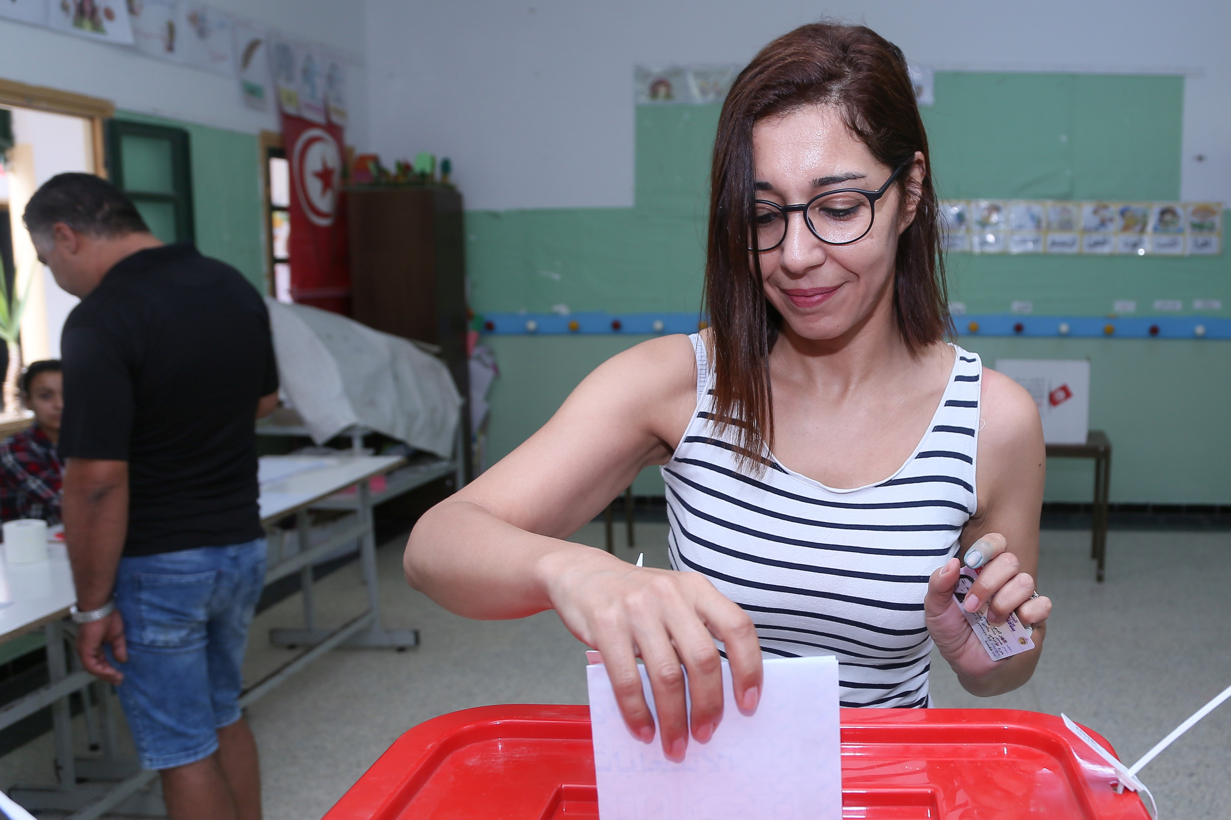 A Tunisian voter casts her ballot for presidential election at a polling station in Sousse on 15 September (AFP)