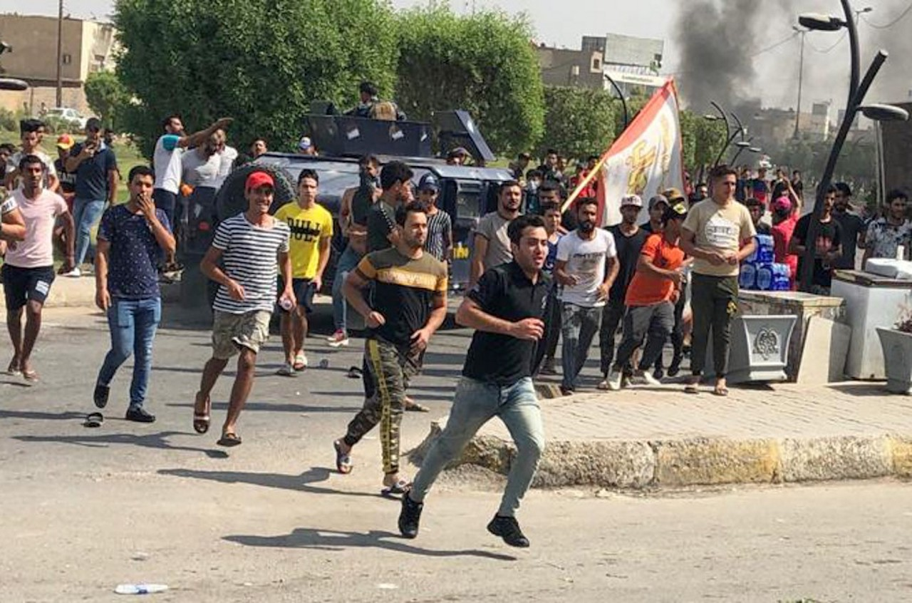 Iraqi protesters run during a demonstration against corruption and lack of basic services in Baghdad's al-Zaafaraniya district (AFP)