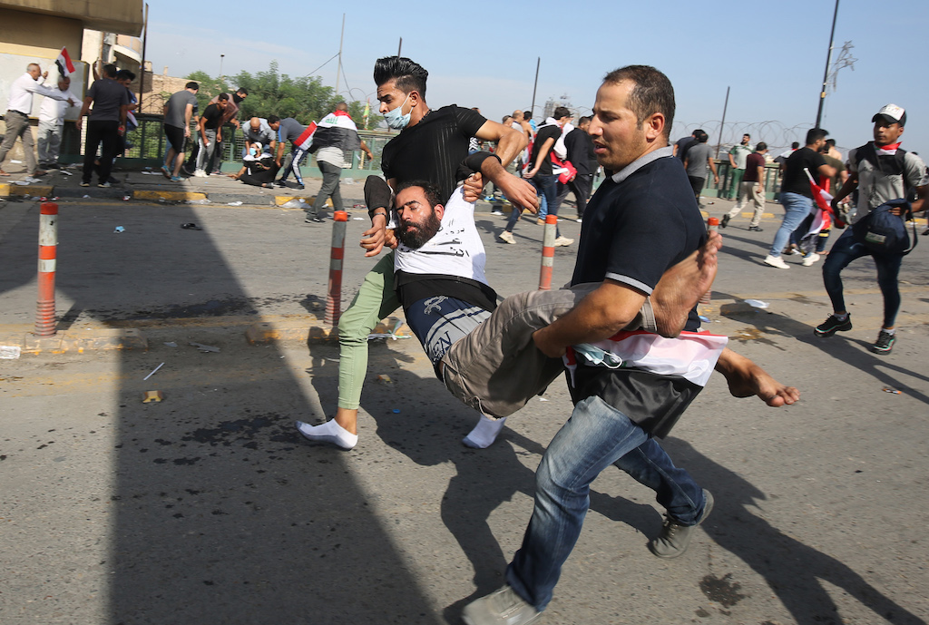 Iraqi protesters carry a comrade who fainted due to tear gas used by security forces to disperse the crowds in central Baghdad during anti-government demonstrations in the Iraqi capital