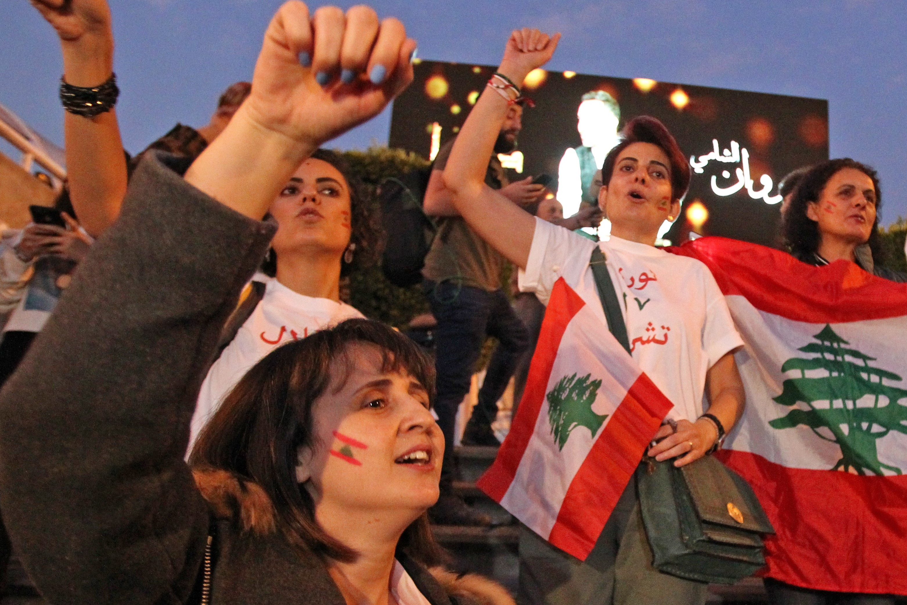 Lebanese expats are welcomed by demonstrators upon their arrival at the Beirut International Airport in the Lebanese capital on 22 November (AFP)