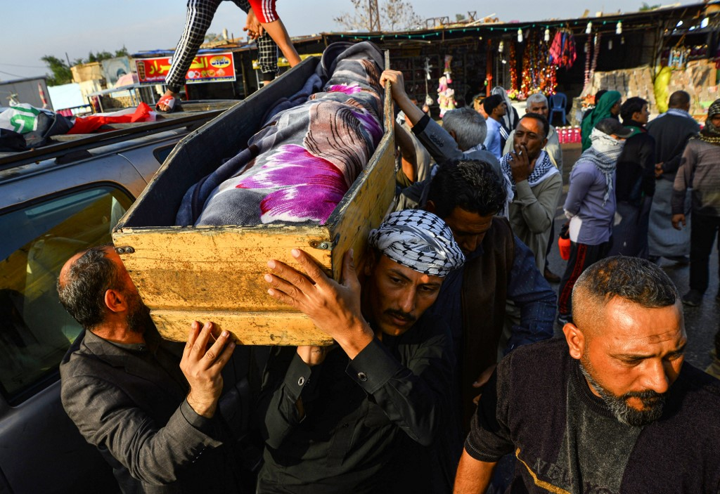 Iraqi mourners carry the coffin of an anti-government protester who was killed in Nasiriyah during clashes between anti-government protesters and security forces in November (AFP)