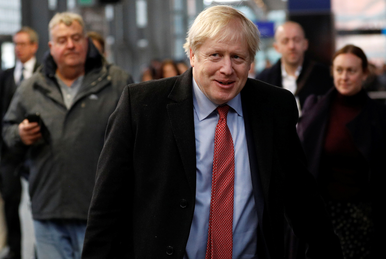 Britain's Prime Minister Boris Johnson reacts as he walks along a platform to board a train ahead of a Conservative Party general election campaign visit, at St Pancras station in London (AFP)