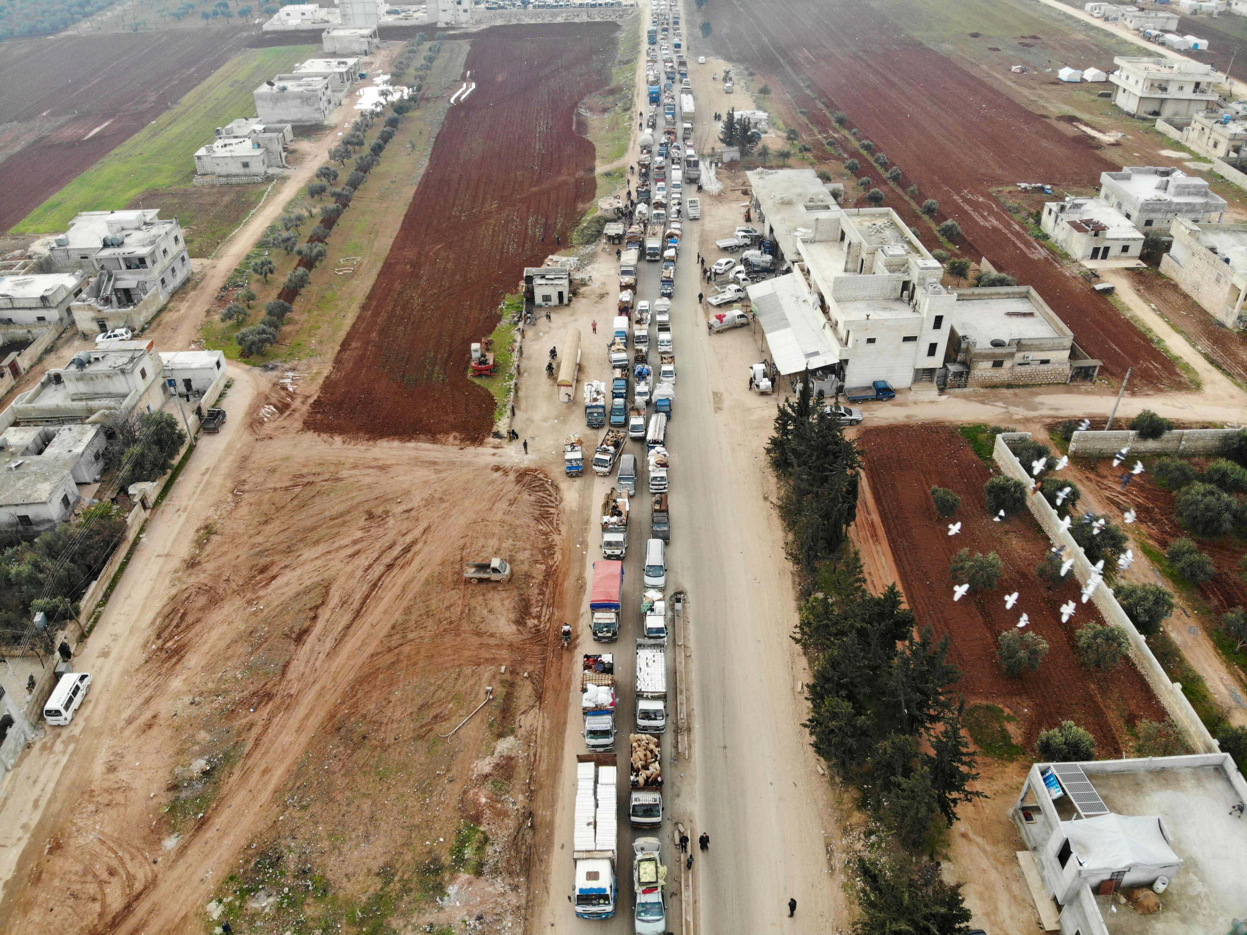 A aerial photo shows displaced Syrians driving through Hazano in the northern countryside of Idlib, after fleeing on 28 January (AFP)