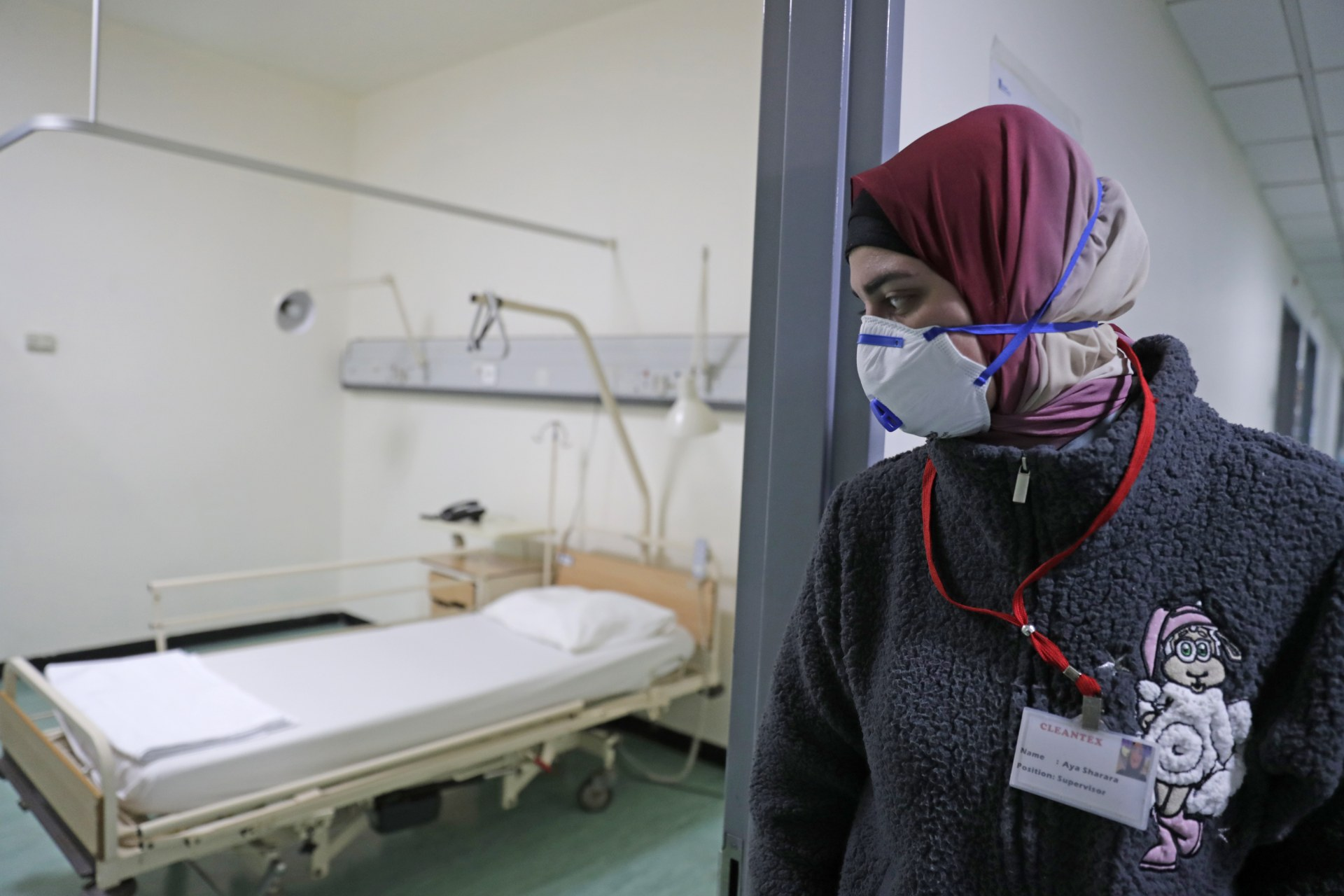A Lebanese employee wearing a protective mask looks at a bed in a ward where the first case of coronavirus in the country is being treated, at the Rafic Hariri University Hospital (AFP)