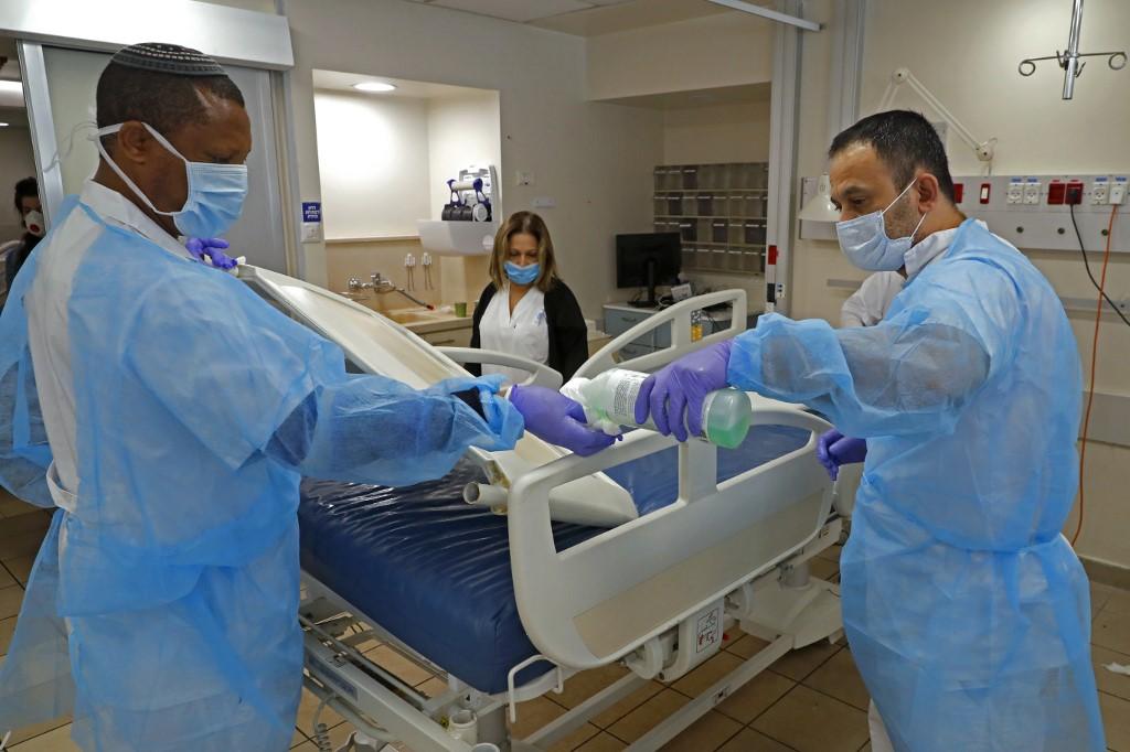 Le personnel du centre médical Sourasky (hôpital Ichilov) à Tel Aviv désinfecte une section dédiée aux malades du COVID-19, le 19 mars 2020 (AFP)