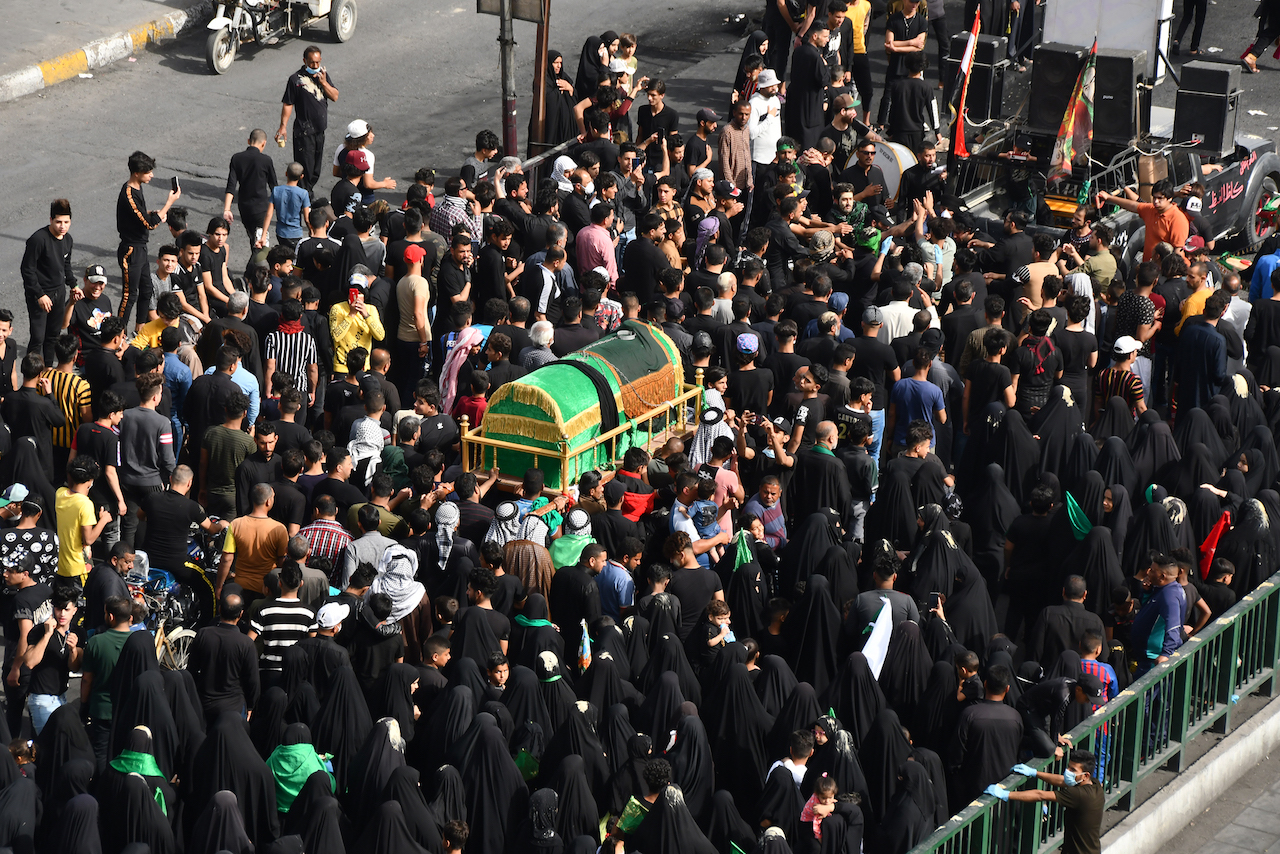 Iraqi Shiite pilgrims carry a mock coffin on their shoulders to mark the anniversary of the death of Imam Moussa al-Kadhim, as they defy a curfew imposed by the authorities to prevent the spread of novel coronavirus COVID-19, in Iraq's southern city of Nasiriyah in Dhi Qar province
