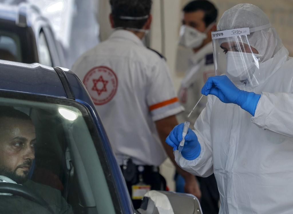 Un ambulancier de Magen David Adom réalise un test pour le COVID-19 dans le quartier palestinien de Jabel Mukaber à Jérusalem-Est annexée, le 2 avril 2020 (AFP)