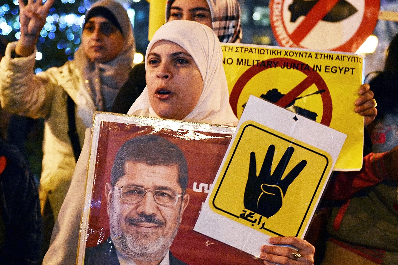 Une femme brandit une bannière de l'ancien président égyptien Mohamed Morsi lors d'une manifestation d'opposition à Sissi à Athènes en décembre2015 (AFP)