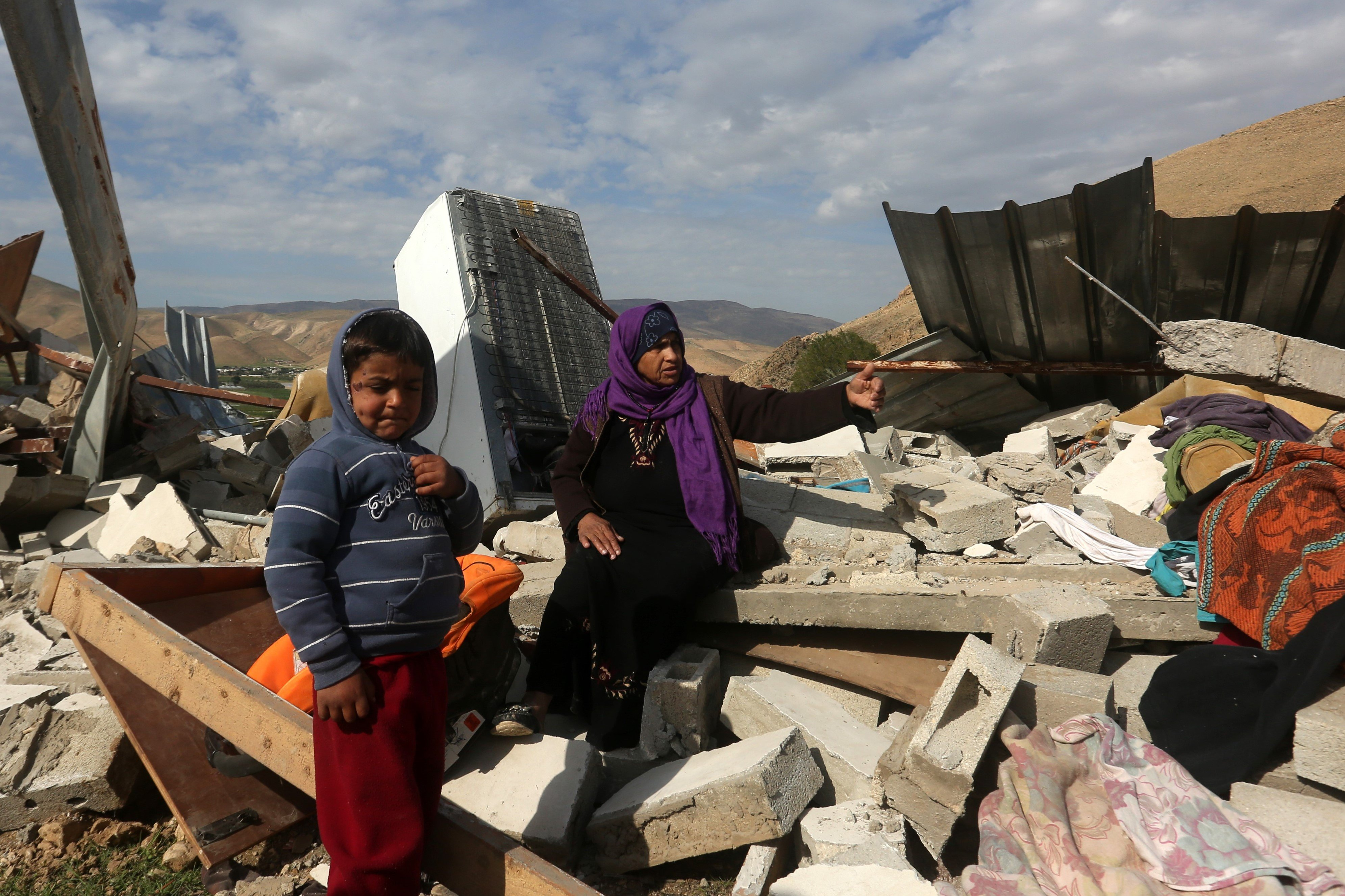 Palestinians check the rubble of their house after it was demolished by Israeli authorities in the West Bank village of Jeftlek