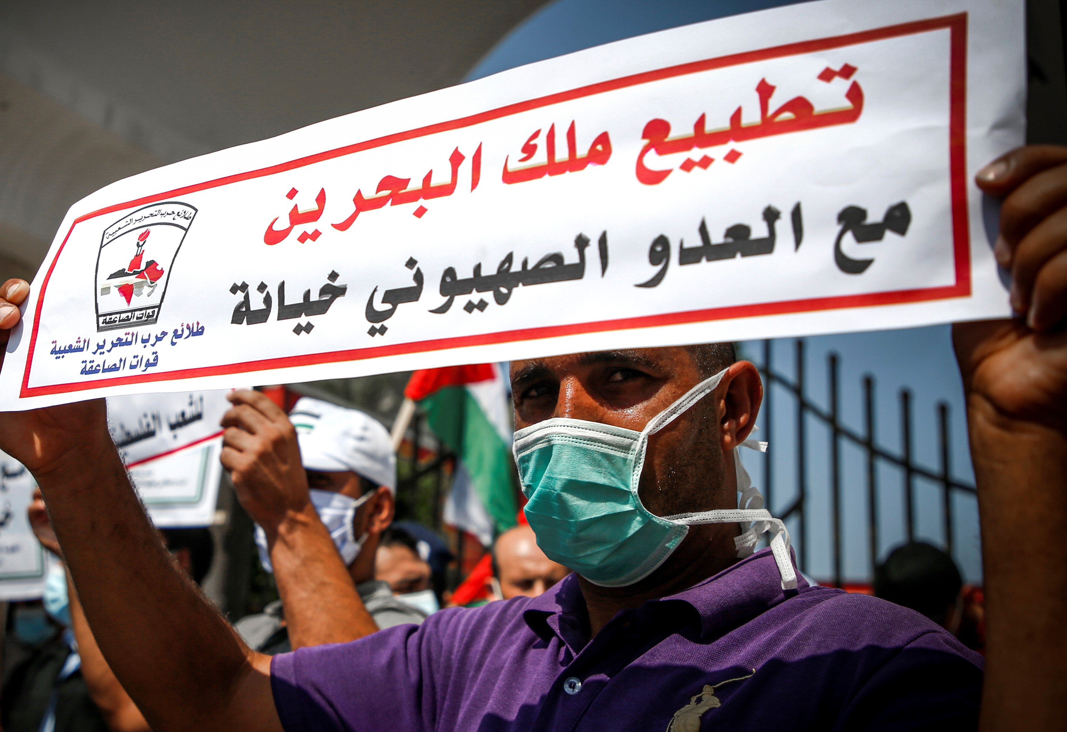 "A demonstrator, mask-clad due to the COVID-19 coronavirus pandemic, stands holding a sign reading in Arabic ""the King of Bahrain's normalisation with Israel is betrayal"" during a protest against the United Arab Emirates' and Bahrain's decisions to normalise relations with Israel, in Gaza City on September 15, 2020."