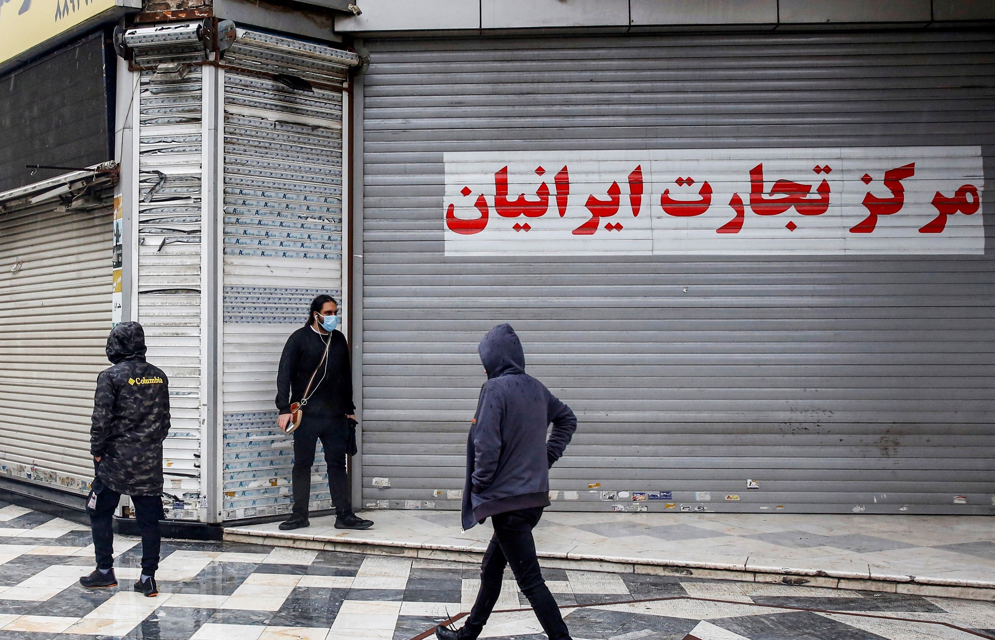 Pedestrians, mask-clad due to the COVID-19 coronavirus pandemic, walk past closed shops along a street in Iran's capital Tehran on November 21, 2020,