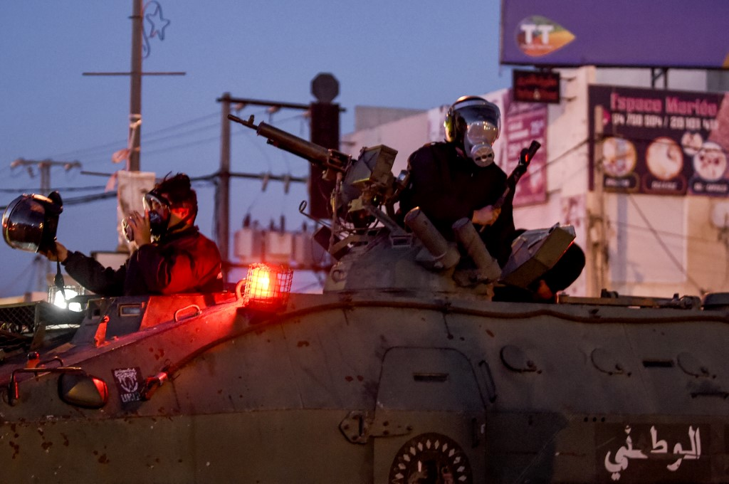 Members of the Tunisian National Guard seated in their armoured vehicles in Ettadhamen on 17 January 2021 (AFP)