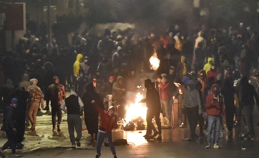 Protesters block a street during clashes with the police in Ettadhamen on 18 January 2021 (AFP)